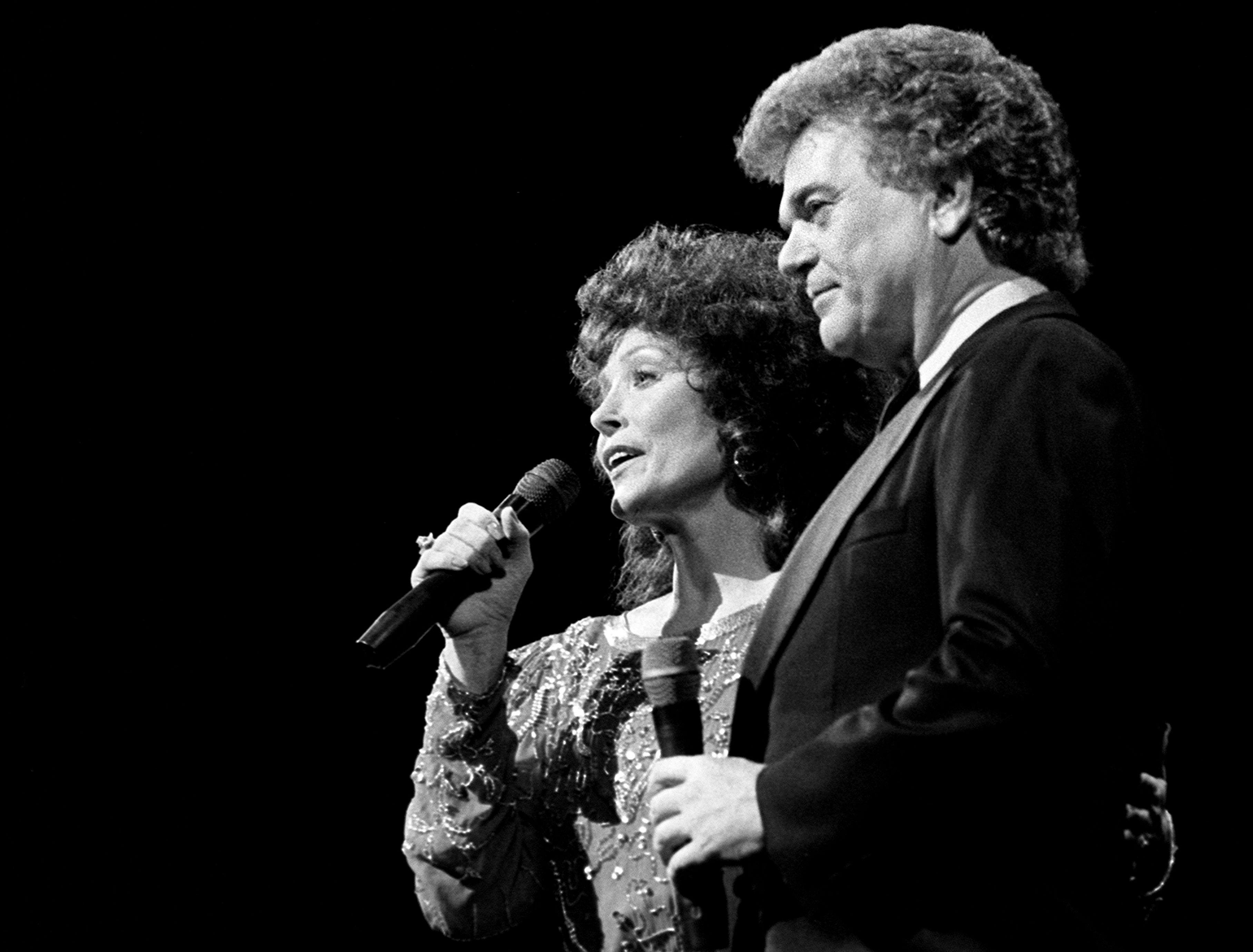 """Loretta Lynn, left, and Conway Twitty reunited onstage to sing a snippet of their """"Louisiana Woman, Mississippi Man"""" during the CMA Awards show at the Grand Ole Opry House Oct. 13, 1986."""