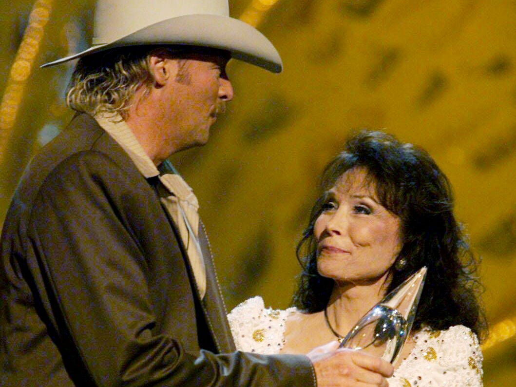 Alan Jackson, left, accepts the Entertainer of the Year award from Loretta Lynn at the 36th annual CMA Awards show at the Grand Ole Opry House Nov 6, 2002.