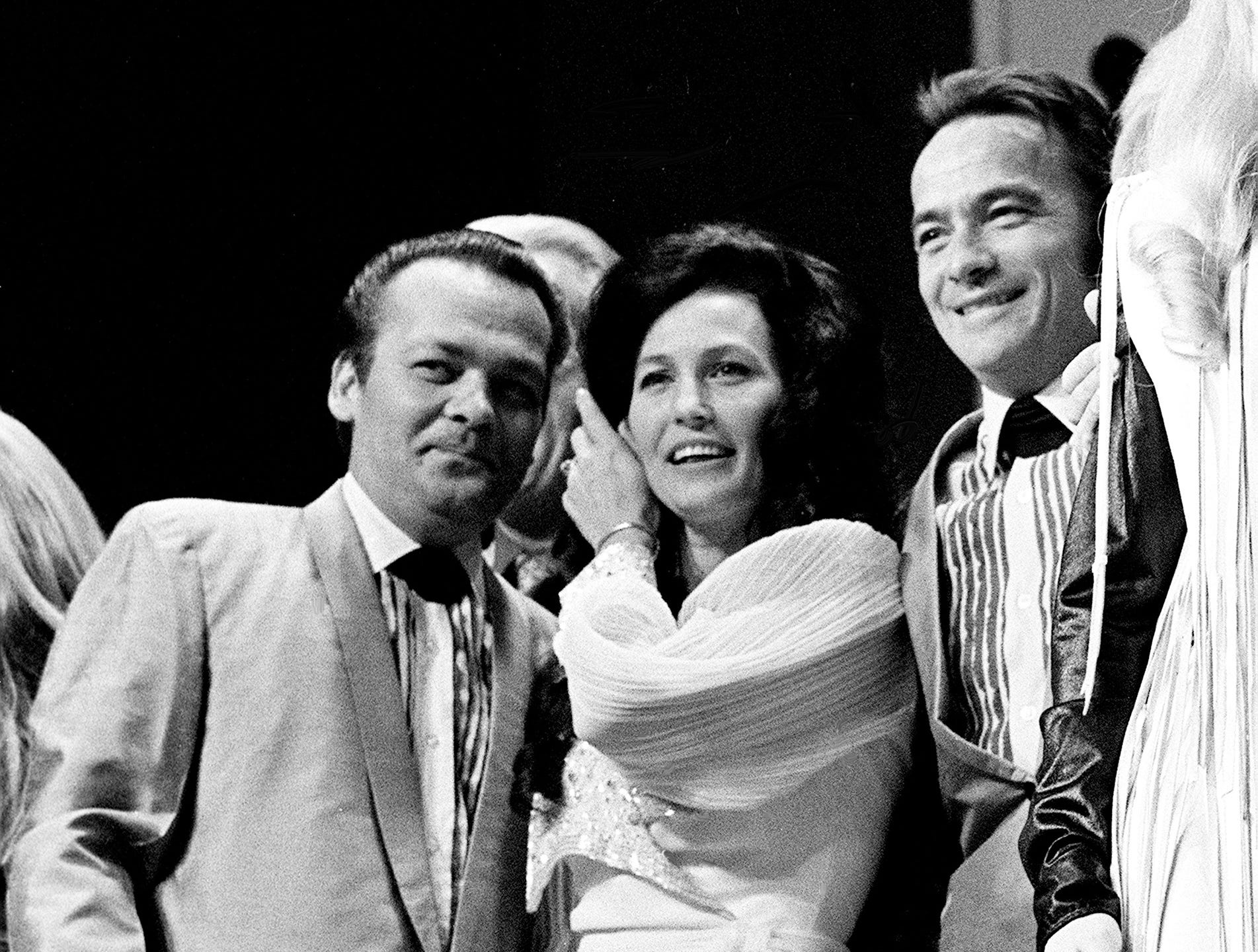 Loretta Lynn, center, is join by Doyle, left, and Teddy Wilburn on stage with other Grand Ole Opry performers at the WSM Luncheon Spectacular on Oct. 15, 1970.