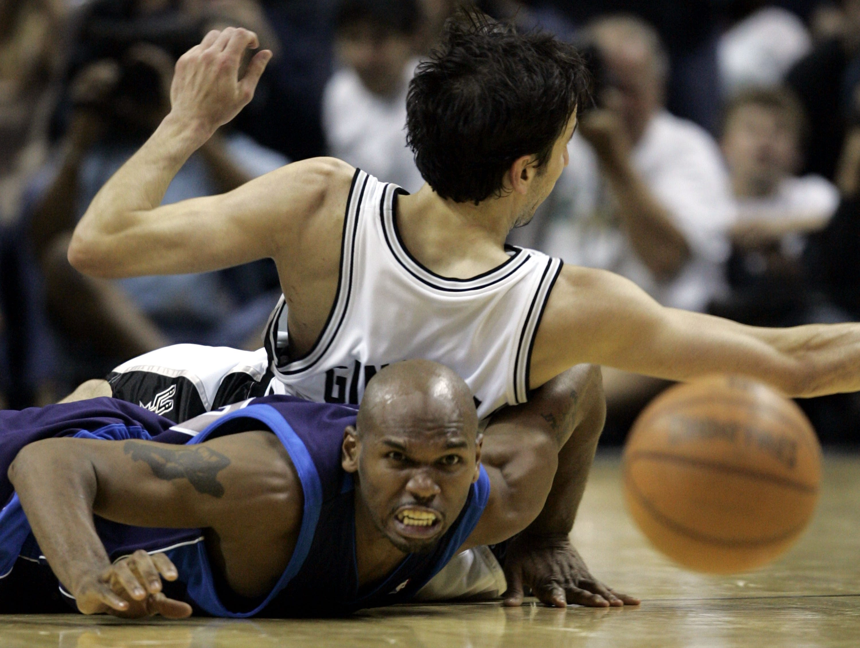 Dallas Mavericks Jerry Stackhouse watches the ball bounce away after making a scramble with it with San Antonio Spurs Manu Ginobili (20) of Argentina in the fourth quarter in Game 5 of the NBA Western Conference semifinal basketball game in San Antonio, Wednesday, May 17, 2006.