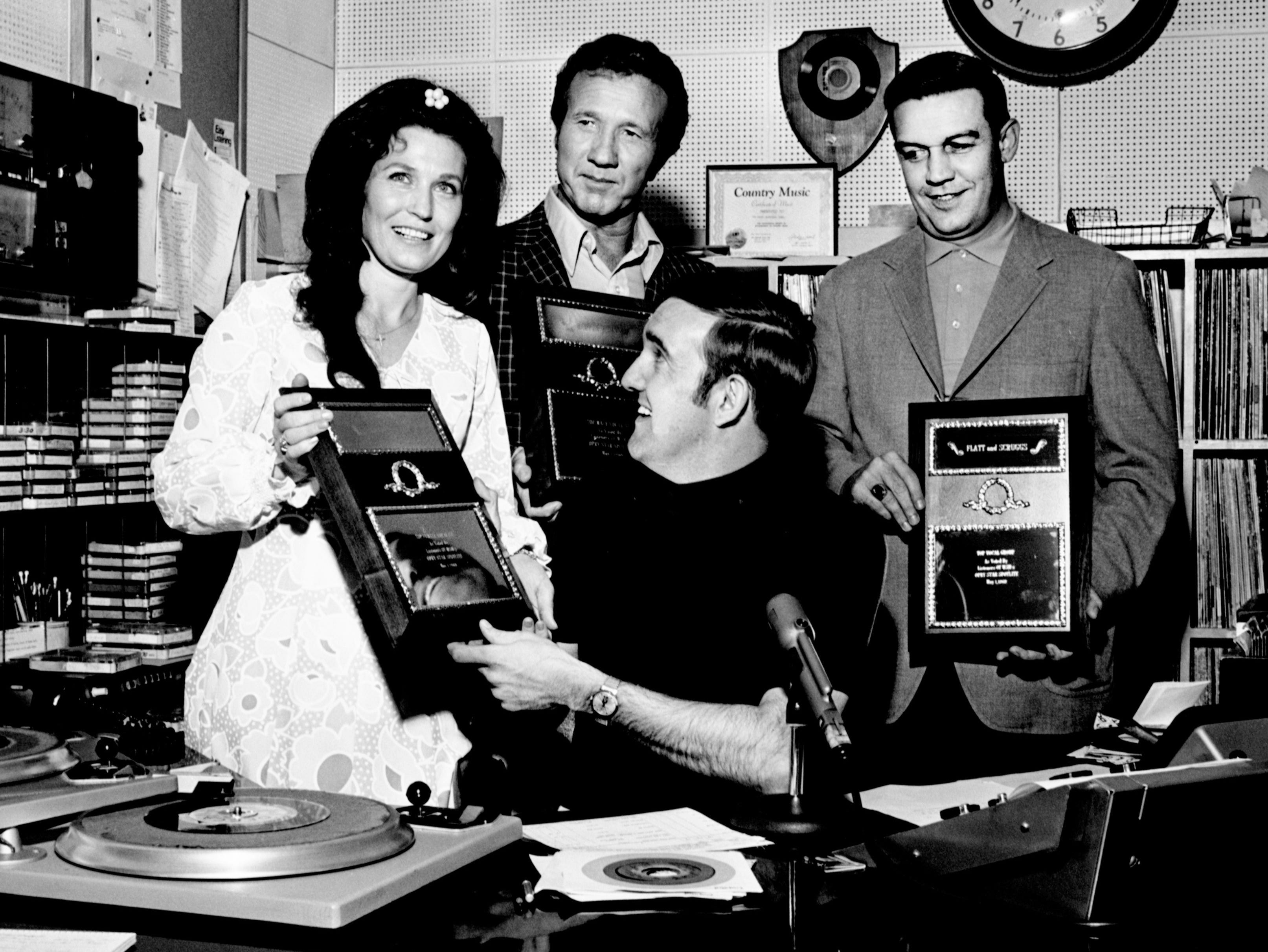 Loretta Lynn, left, and Marty Robbins show off their Top Female and Male vocalist awards as voted by listeners of WSM Opry Star Spotlight for May 1, 1969. Ralph Emery, seated, of WSM, presents the awards at the WSM-TV studio on May 19, 1969, as Bud Wendell, right, holds the Top Vocal Group award won by Flatt and Scruggs.