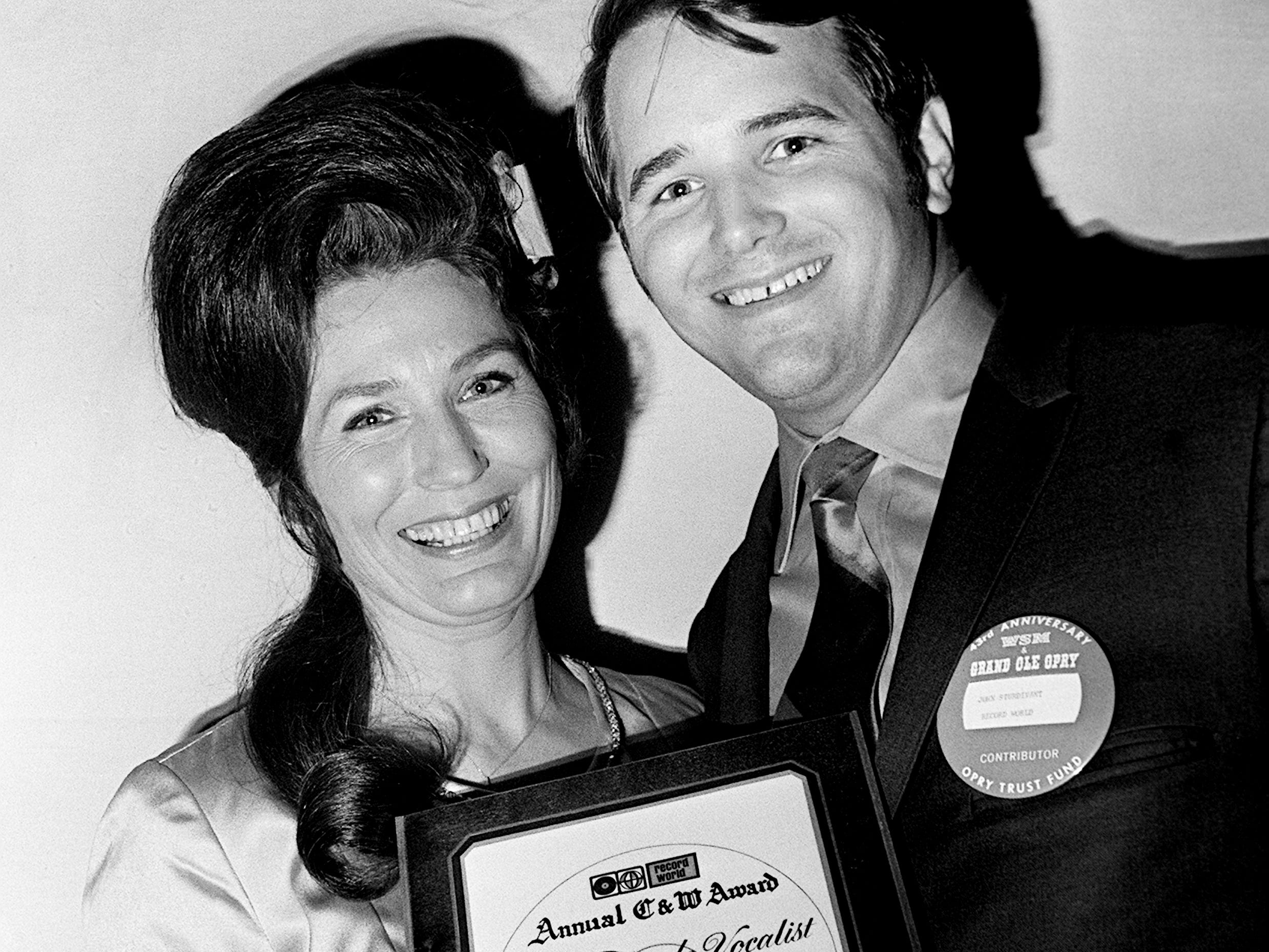Loretta Lynn received the annual Top Female Vocalist award for 1968 from Jack Sturdivant of Record World backstage the Grand Ole Opry 43rd birthday party show Oct. 19, 1968.