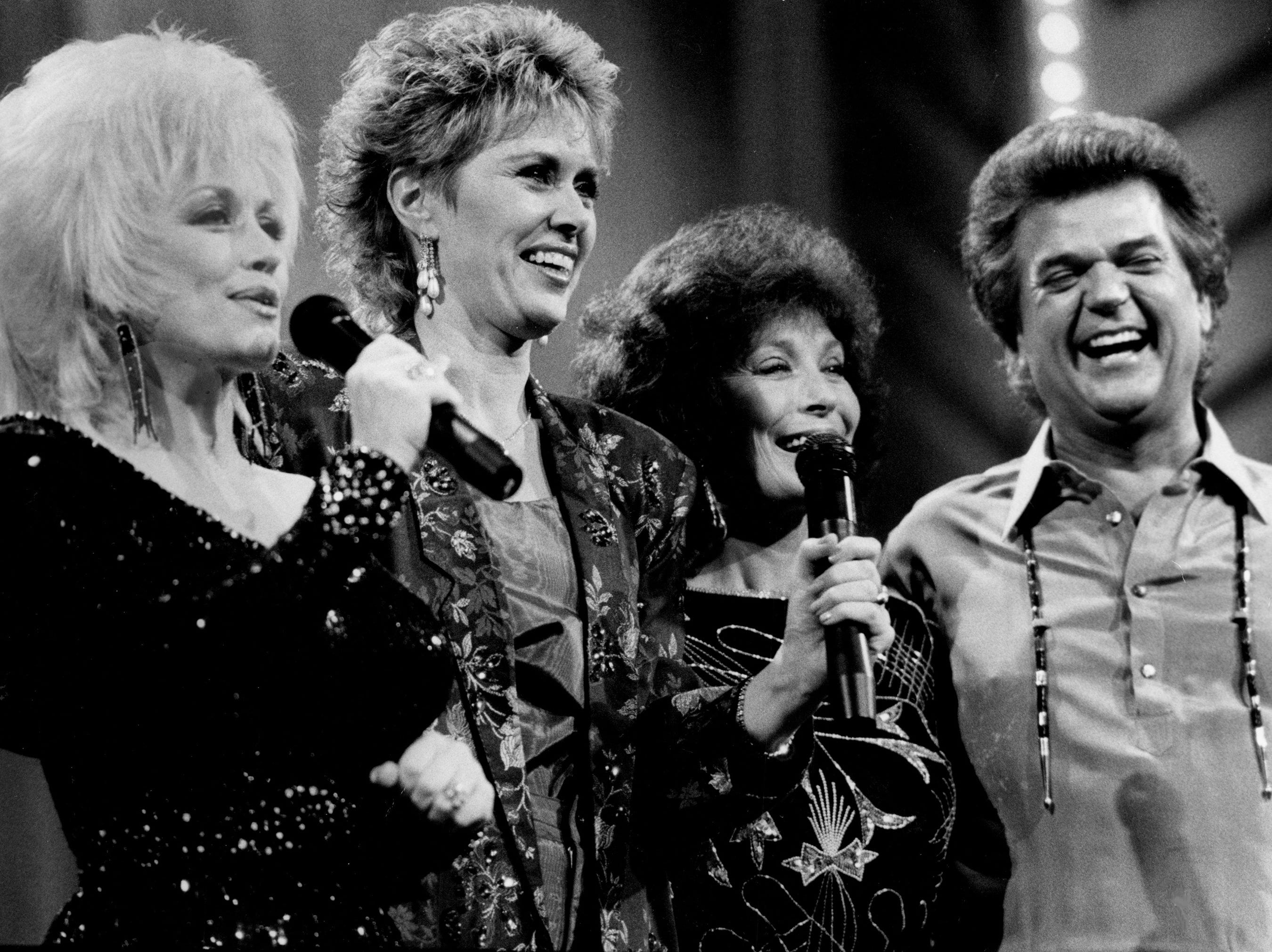 Dolly Parton, left, Janie Fricke, Loretta Lynn and Conway Twitty conclude a segment of the fan-voted Music City News Awards show celebrating the annual event's 20th anniversary June 9, 1986. Lynn was honored with the Living Legend award and had a reunion with Twitty.