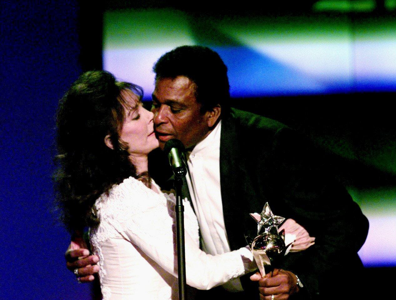A surprised Charlie Pride, right, accepts the Living Legend award from presenter Loretta Lynn at the 31st TNN/Music City News Award show at the Grand Ole Opry House June 16, 1997.