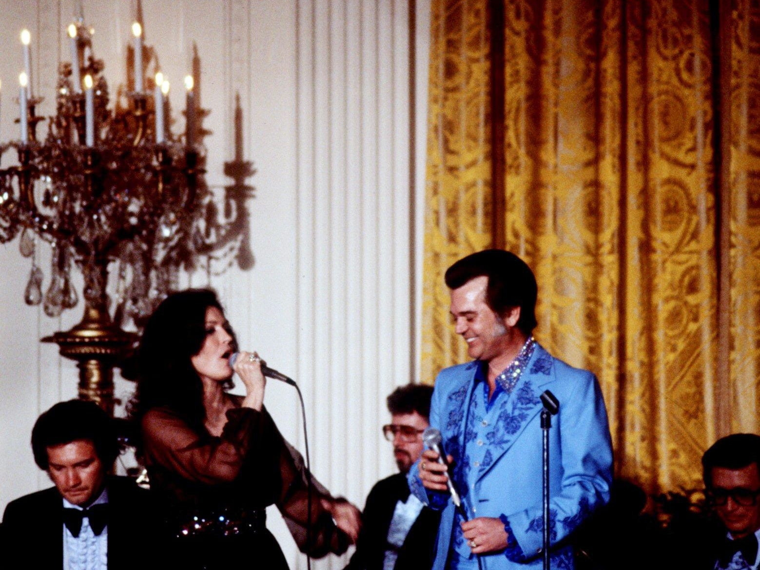 """Loretta Lynn, left, and Conway Twitty sing out with """"Louisiana Women, Mississippi Man,"""" under a sparkling chandelier of the East Room of the White House during country music night in Washington, D.C. April 17, 1978. More than 200 guests attended a gala reception give by President and Mrs. Jimmy Carter honoring the CMA."""