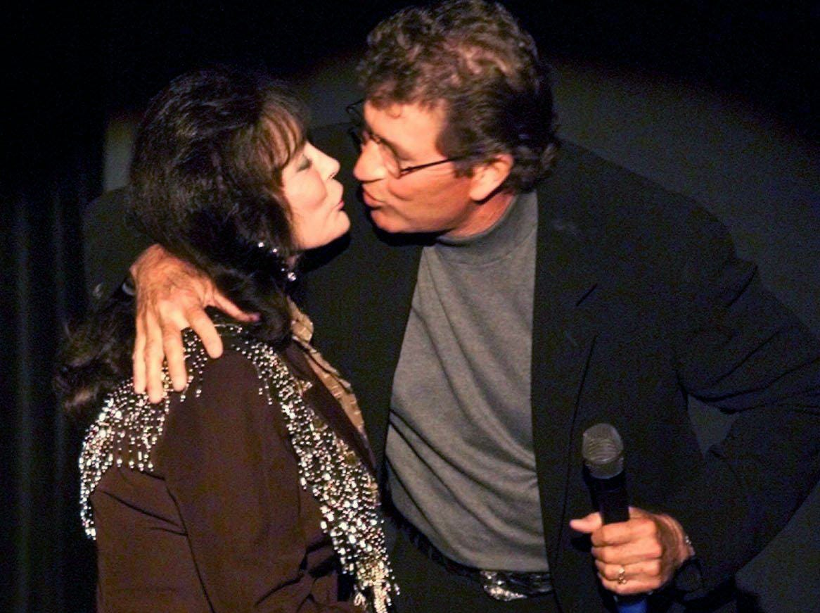 Loretta Lynn, left, gets a kiss from songwriter Mac Davis as she takes the stage during the Tin Pan South Legendary Songwriters Acoustic concert at the Ryman Auditorium April 4, 2000.