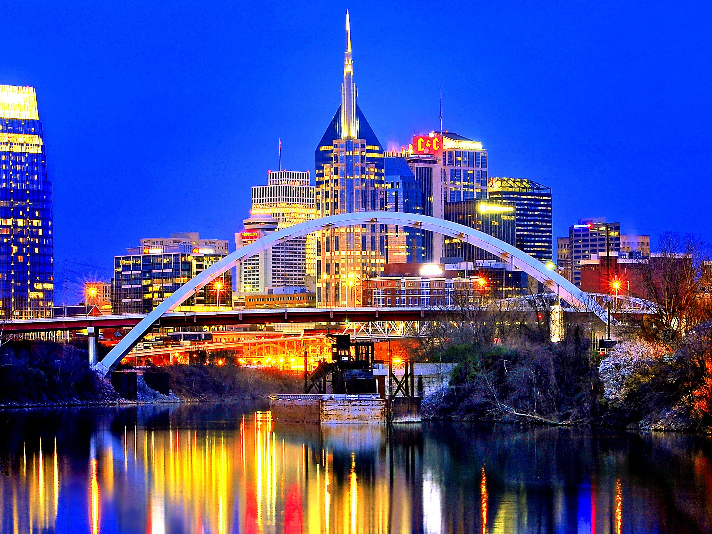 Lights from the Nashville skyline are reflected in the Cumberland River which flows through downtown on March 28, 2013.