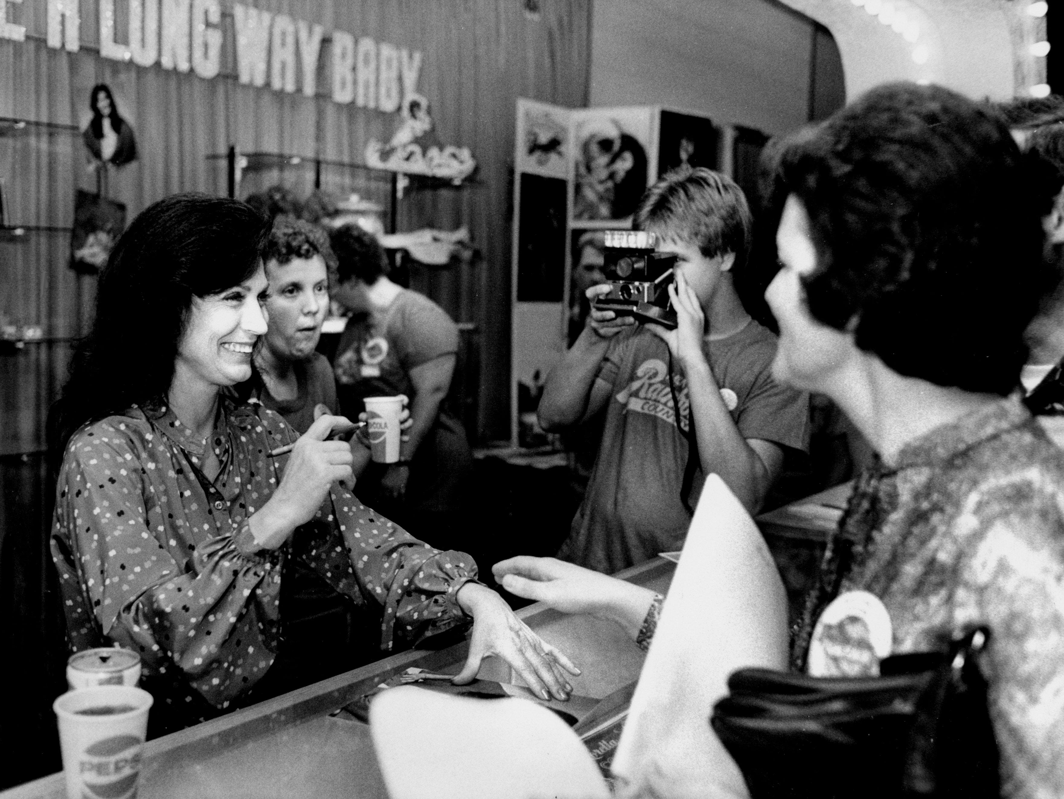 Loretta Lynn, left, greets some of the many fans who waited to see her for more than two hours during Fan Fair at the Municipal Auditorium June 7, 1979.