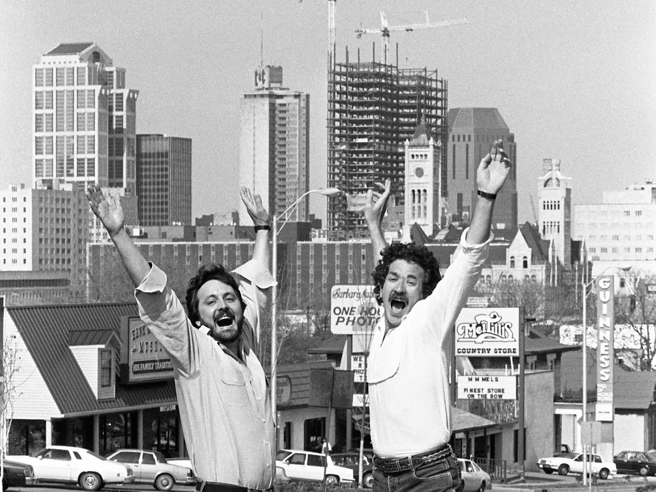 "Songwriters Chris Waters, left, and Kix Brooks, selected as composers of Nashville's official theme song, are celebrating their triumph with the city's growing skyline behind them April 1, 1986. Their song, ""I Still Hear The Music of Nashville,"" will be premiere during the Summer Lights celebration by the Nashville Symphony and a star guest vocalist."