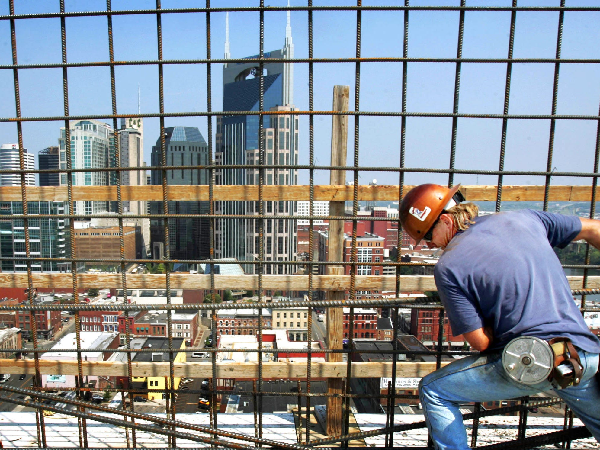 With the Nashville skyline in the background, Jeno Harmon installs rebar as he works on the top floor of the Encore building on Third Ave South July 26, 2007.