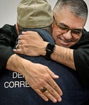 Dr. Eduardo Rocha embraces an inmate after a revival meeting in the gym at Riverbend Maximum Security Institution on March 31.
