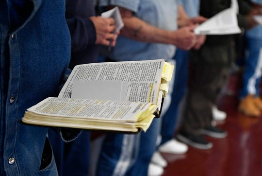 An inmate holds a bible as the chaplain at Riverbend Maximum Security Institution, Dr. Eduardo Rocha, reads the scripture on March 31.