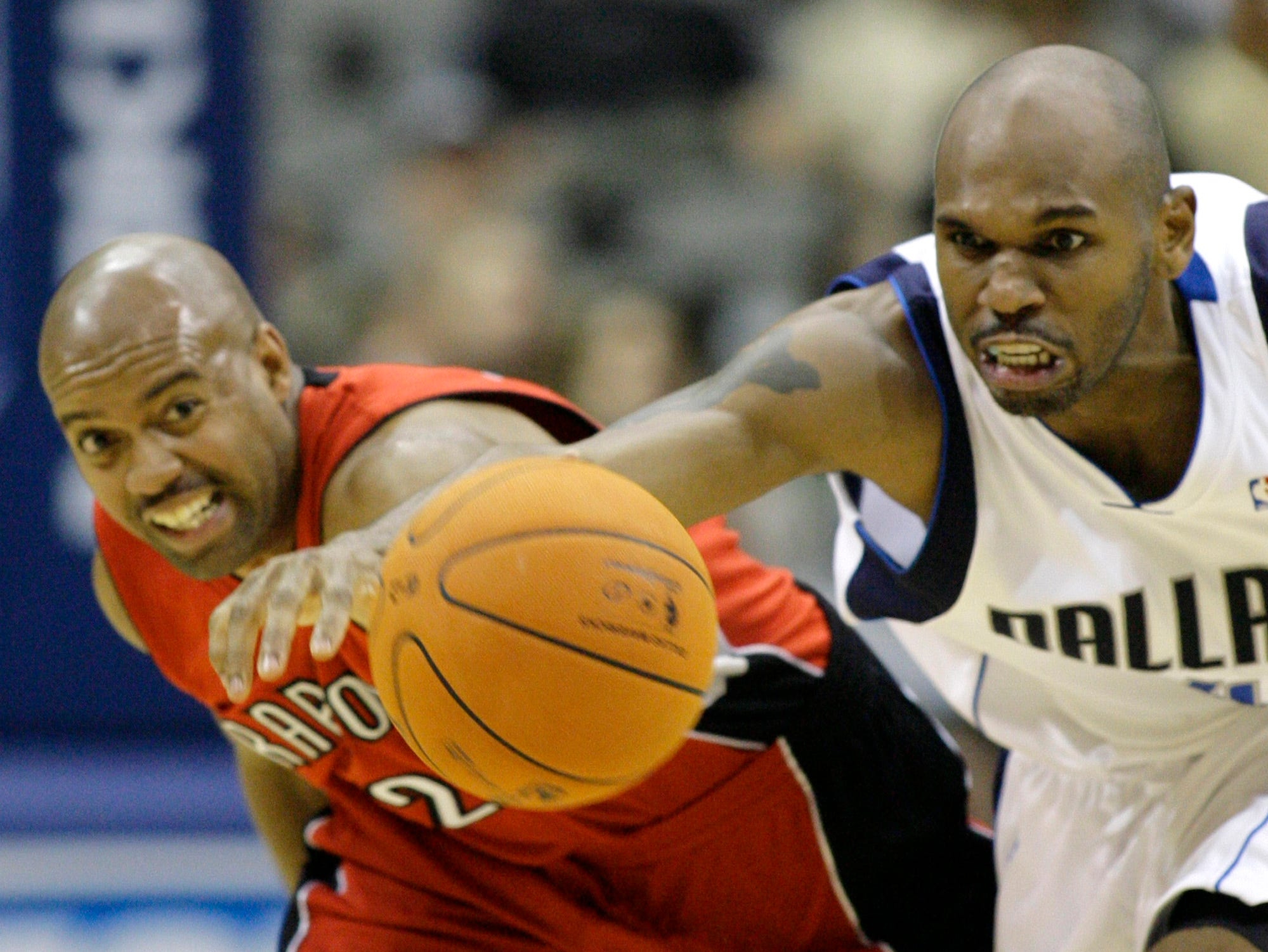 Dallas Mavericks guard Jerry Stackhouse, right, and Toronto Raptors guard Darrick Martin reach for a loose ball during the second half of an NBA basketball game Wednesday, Nov. 29, 2006, in Dallas. Dallas won 117-98.