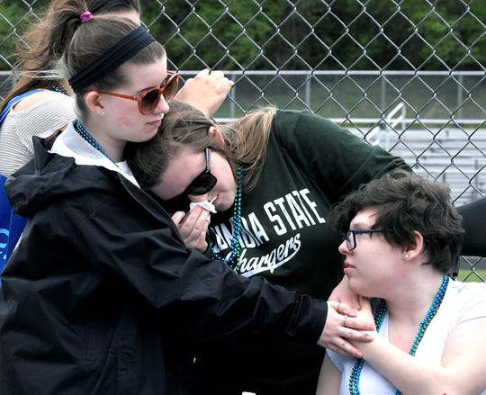 """Volunteers embrace during the opening ceremony of the fourth annual """"Out of the Darkness"""" suicide awareness walk at Centennial High School in Franklin on March 30, 2019."""