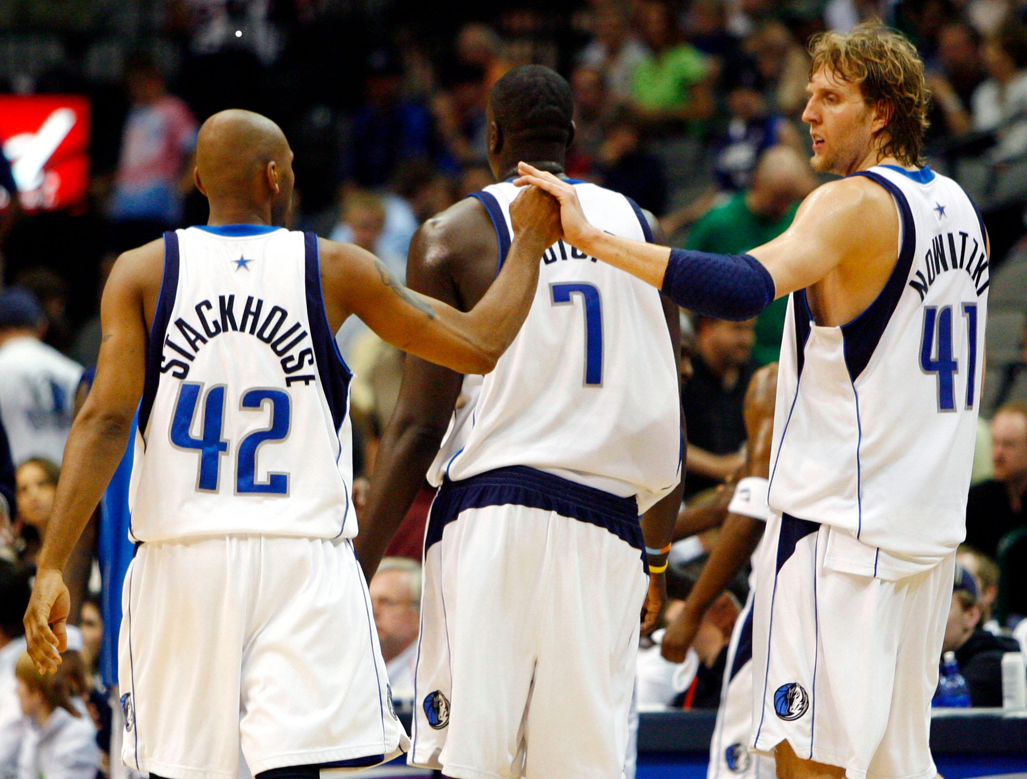 Dallas Mavericks guard Jerry Stackhouse (42) and forward Dirk Nowitzki (41), of Germany, celebrate while walking back to the bench with center DeSagana Diop (7), of Senegal, during a timeout in the second half of an NBA basketball game against the Utah Jazz on Sunday, April 16, 2006, in Dallas. Dallas won 111-95.