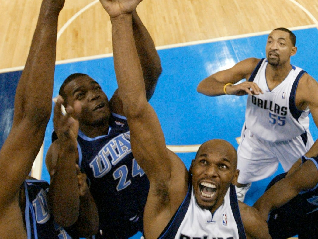 Dallas Mavericks forward Jerry Stackhouse (42) reaches for a rebound against Utah Jazz's Paul Millsap (24) and Jarron Collins, left, during the first half of an NBA basketball game in Dallas, Saturday, Dec. 8, 2007. Mavericks' Juwan Howard (55) looks on from the rear.