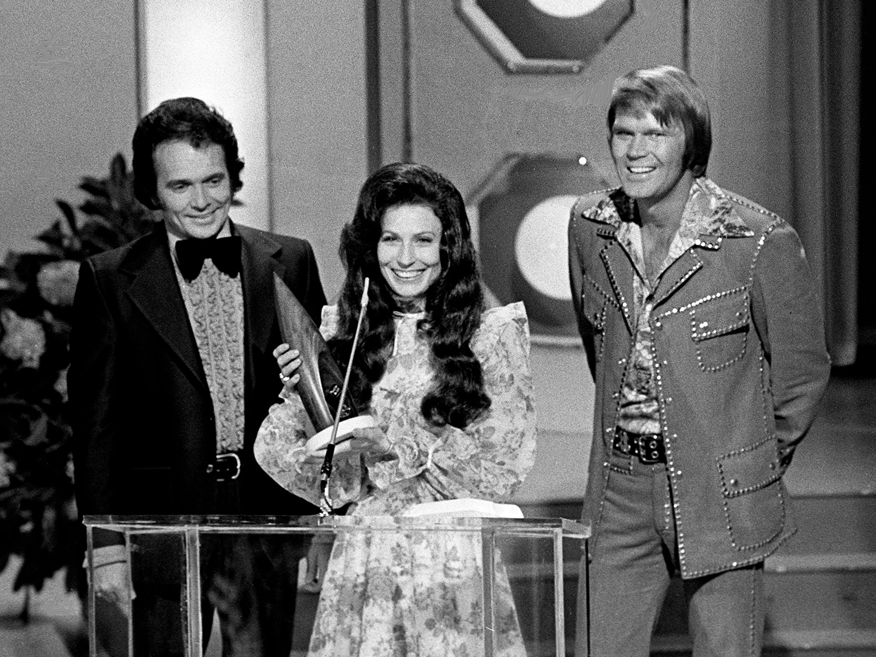 Loretta Lynn, center, accepts the Female Vocalist of the Year award at the seventh annual Country Music Awards show at the Ryman Auditorium. Looking on are presenters Merle Haggard, left, and Glen Campbell.