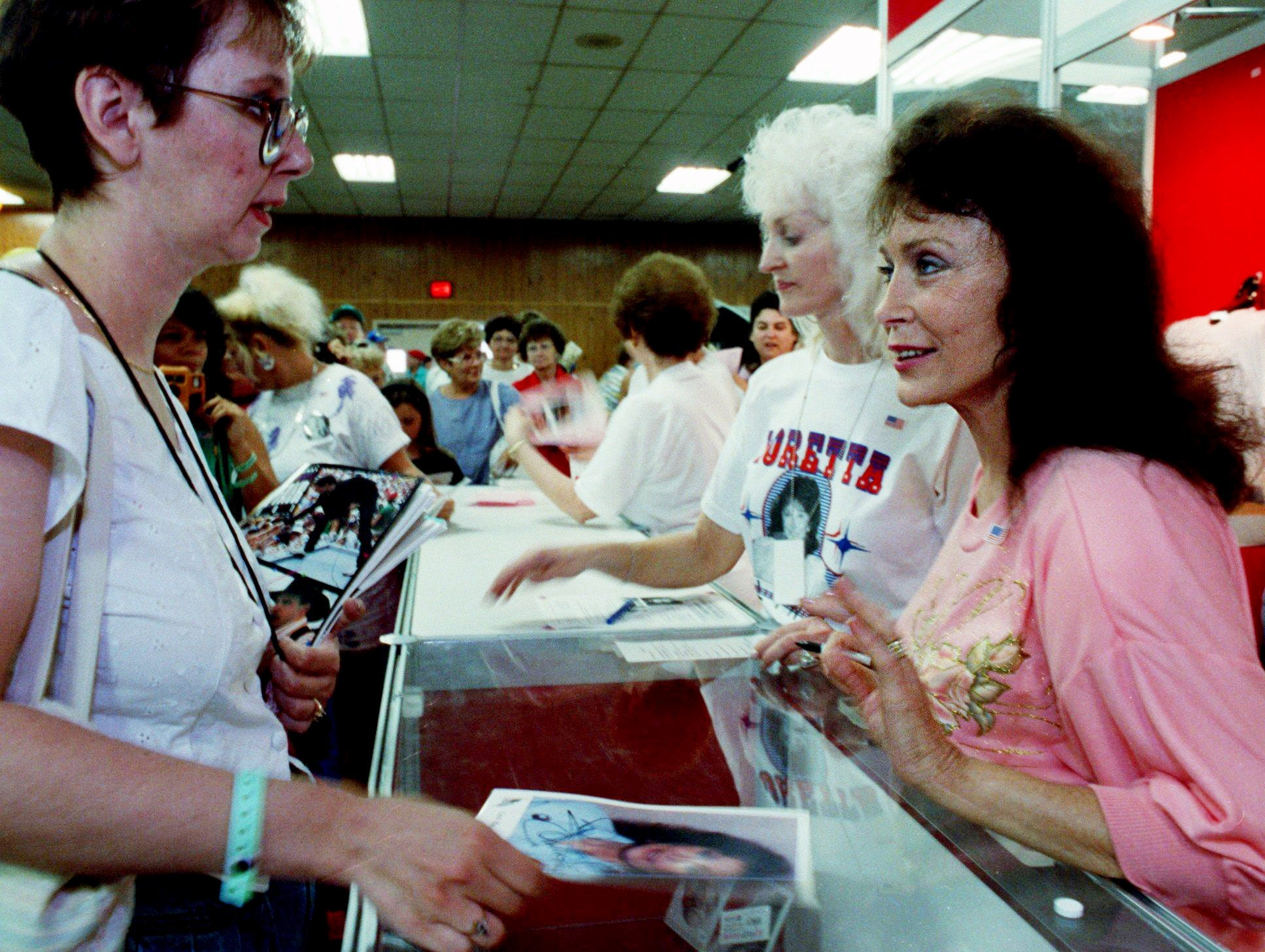 Loretta Lynn, right, greets the latest in a long line of fans, many of whom waited hour and hour to meet her at the Fan Fair get-together at the Tennessee State Fairgrounds June 11, 1991.