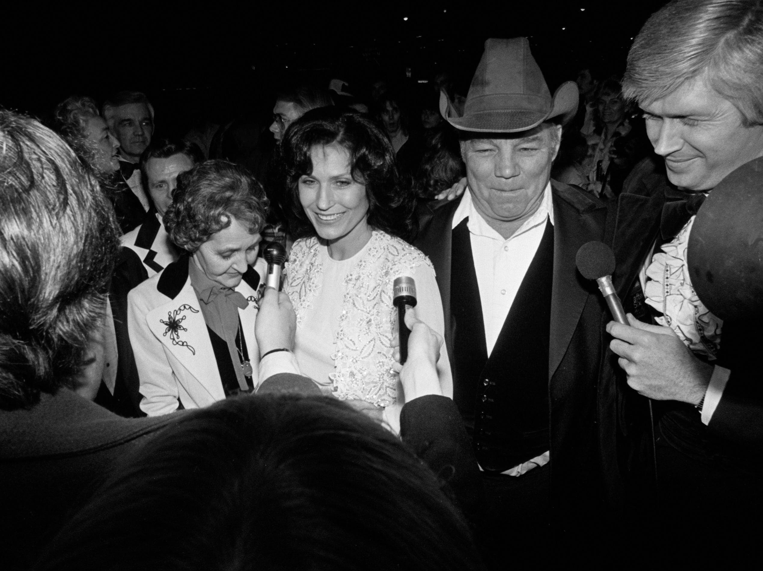 """Loretta Lynn, center, arrives at Belle Meade Theater in the drizzling rain for the movie premiere of """"Coal Miner's Daughter"""" with her mother, Clara Butcher, left, and her husband, Mooney Lynn, March 4, 1980."""