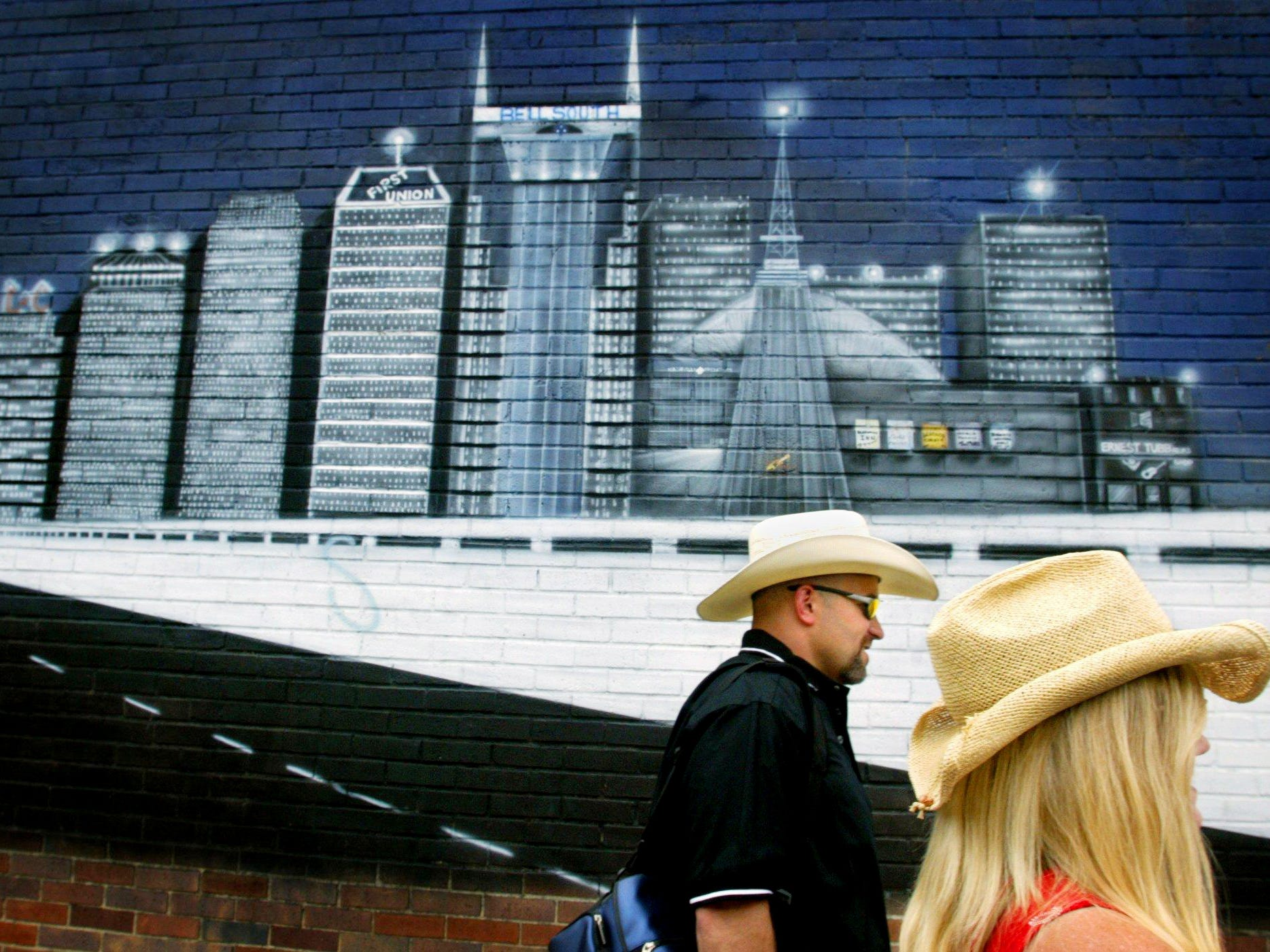 Jim and Dawn Stiveson walk past the mural of the Nashville skyline on the west side of Legends Corner which is next door to the Ryan Auditorium in downtown Nashville June 12, 2003.