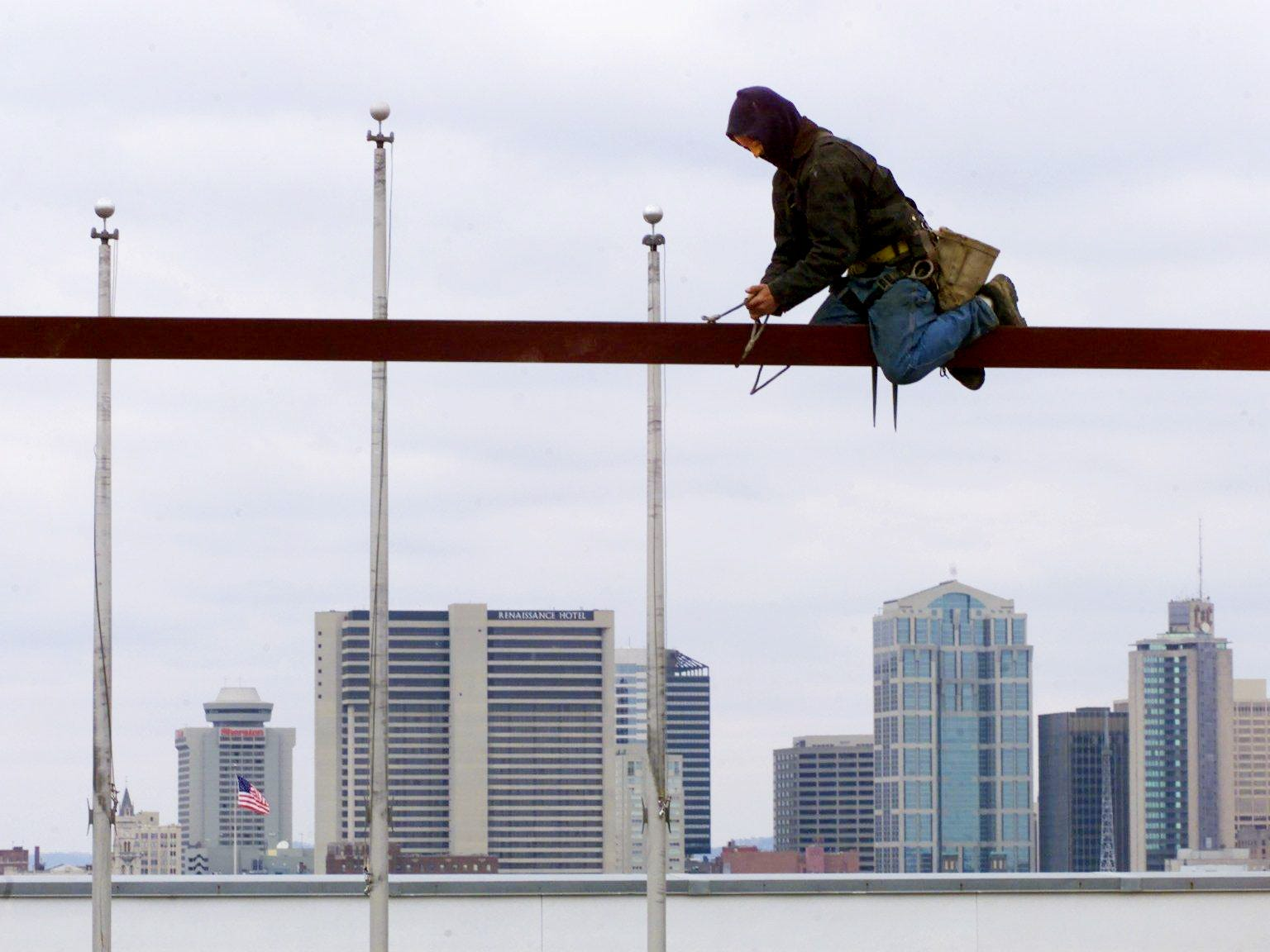 With Nashville's skyline behind him, Derick Dodson straddles a beam as the frame of a 36' glass pyramid rises above the Cumberland Science Museum Feb. 22, 2002.