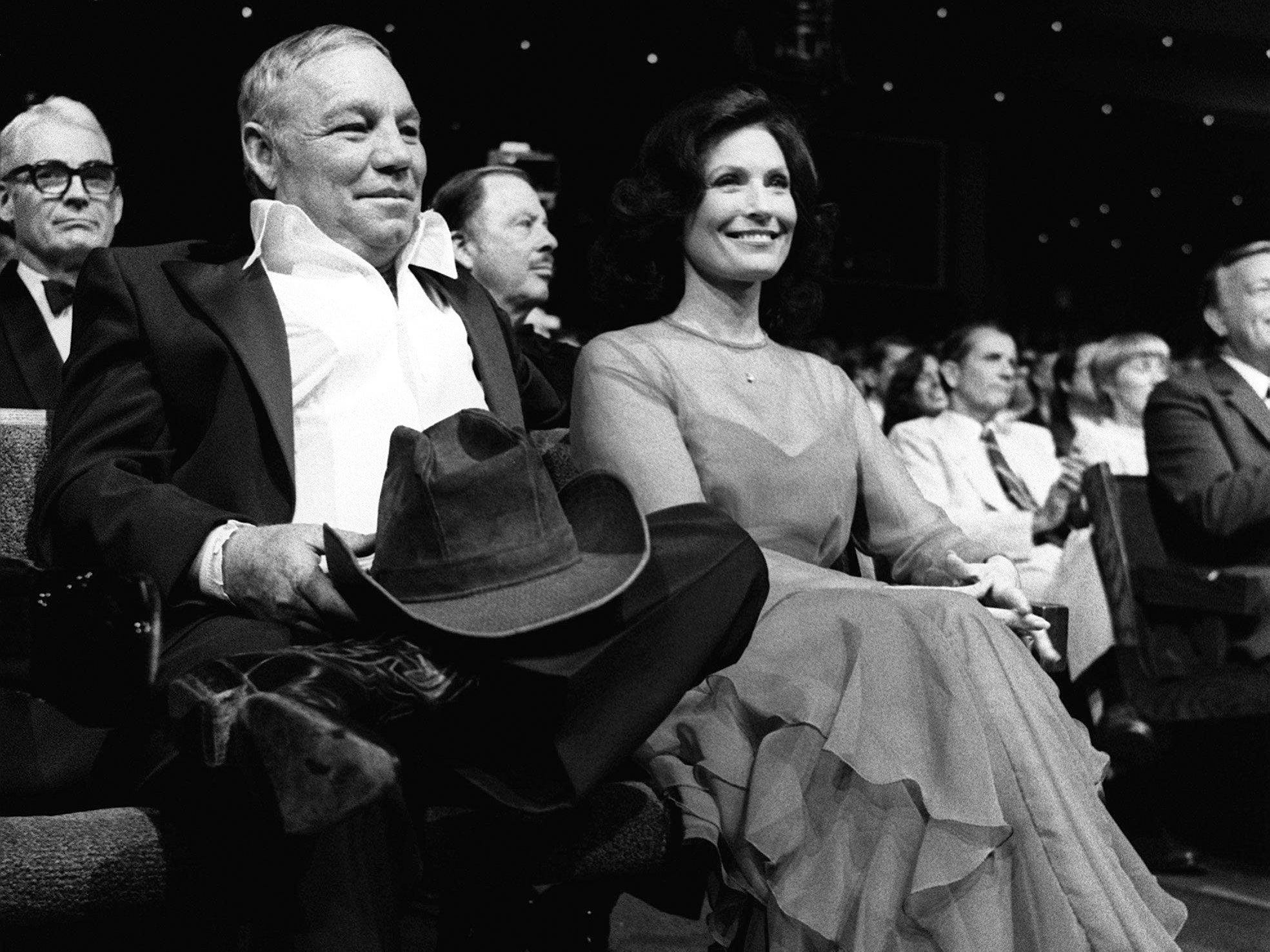 """Loretta Lynn, right, and her husband, Mooney Lynn are in the audience at the 14th annual CMA Awards show at the Grand Ole Opry House Oct. 13, 1980. Lynn accepts the award for the Album of the Year by the original movie sound track from """"Coal Miner's Daughter."""""""