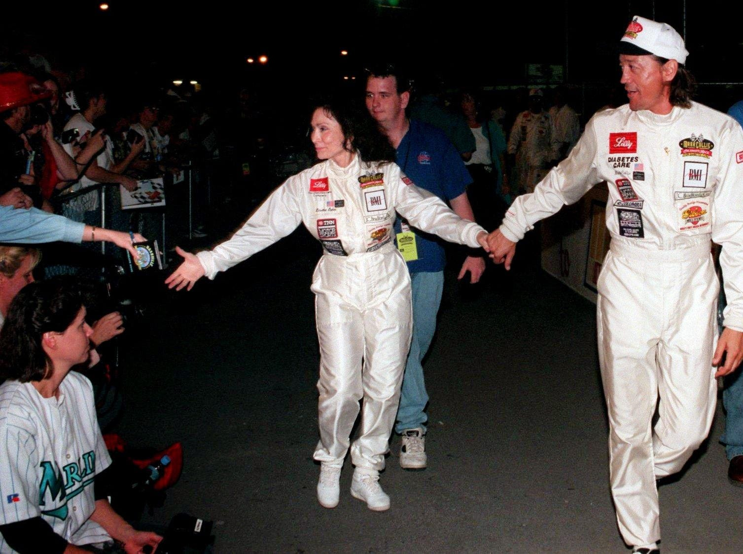 Loretta Lynn, center, and Mark Collie, right, make their way to the stage at the Mark Collie celebrity legends race at Nashville Speedway Oct. 4, 1997.