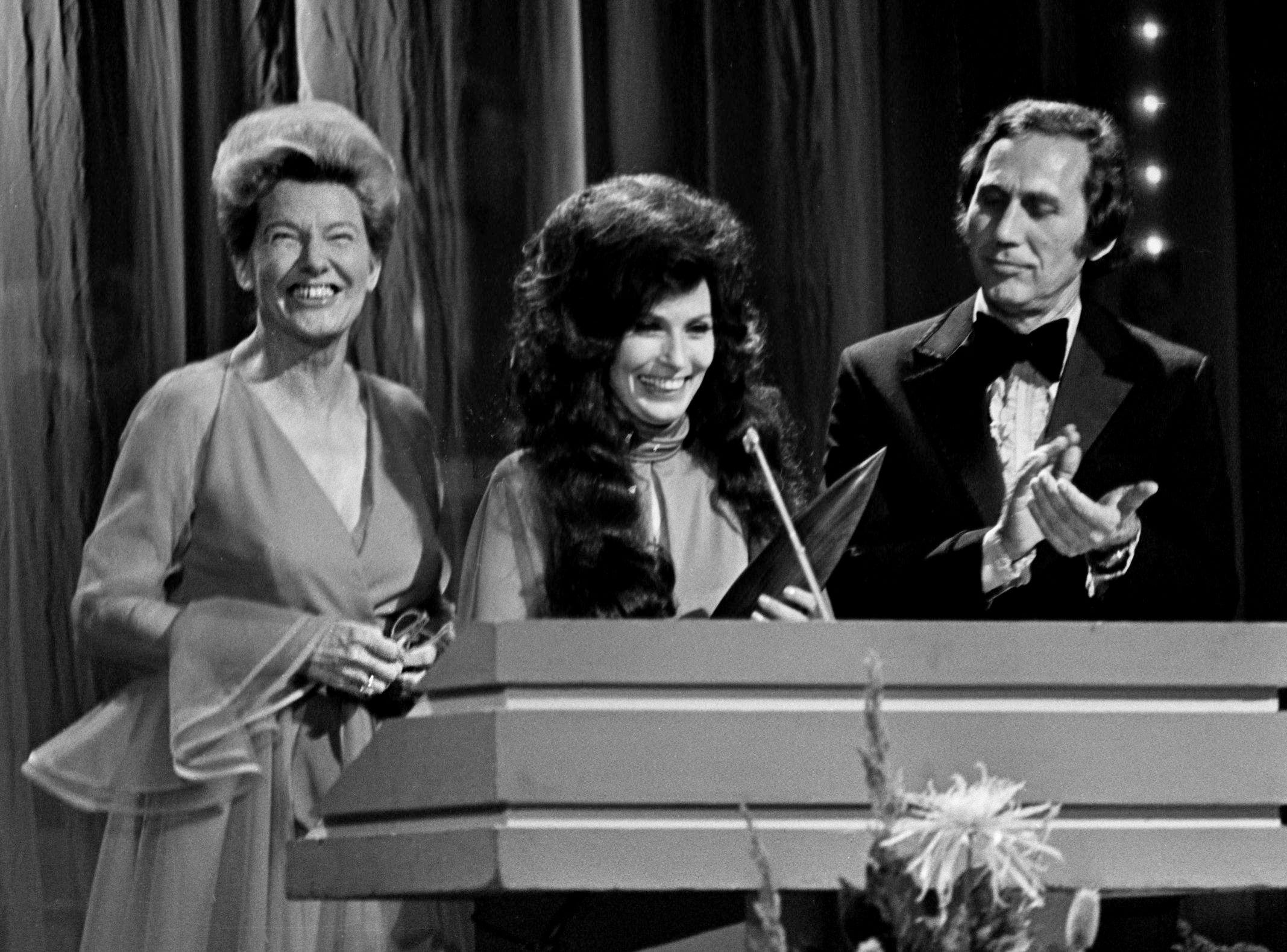 Presenters Minnie Pearl, left, and Chet Atkins, right, welcomes Loretta Lynn, center, to the ranks of CMA Entertainer of the Year during the annual CMA Awards show's nationally televised ceremonies at the Grand Ole Opry House on Oct. 16, 1972.