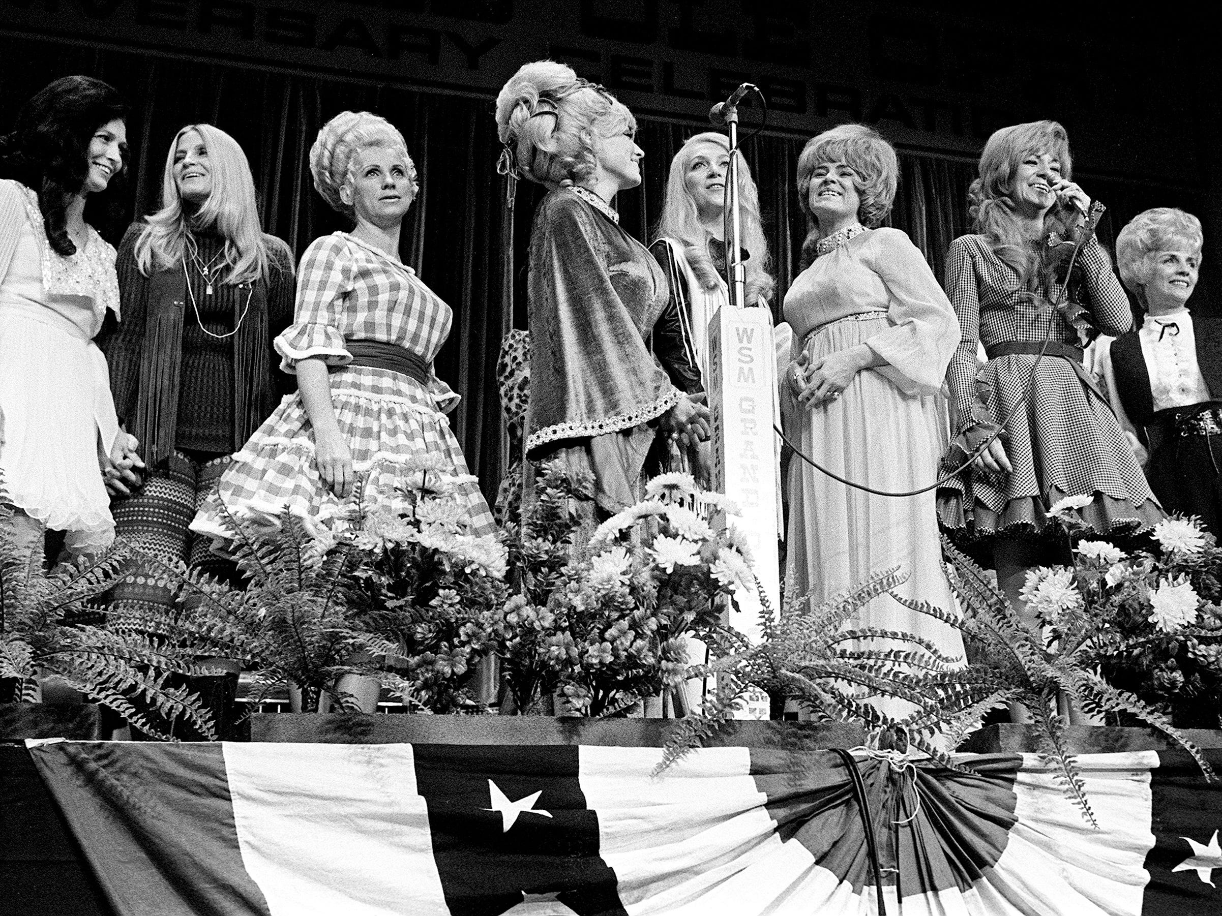 """As Grand Ole Opry star Dottie West, third from right, sings """"Born To Be A Country Girl"""" on the WSM Luncheon Spectacular on Oct. 15, 1970, all the other Opry girls filter out on the stage to help. They are Loretta Lynn, left, Skeeter Davis, Mrs. Ben Smathers, Dolly Parton, Jeanie Seely, Margie Bowes, Del Wood (behind Bowes), Miss West, Minnie Pearl (behind West), Marion Worth and Jean Shepard."""