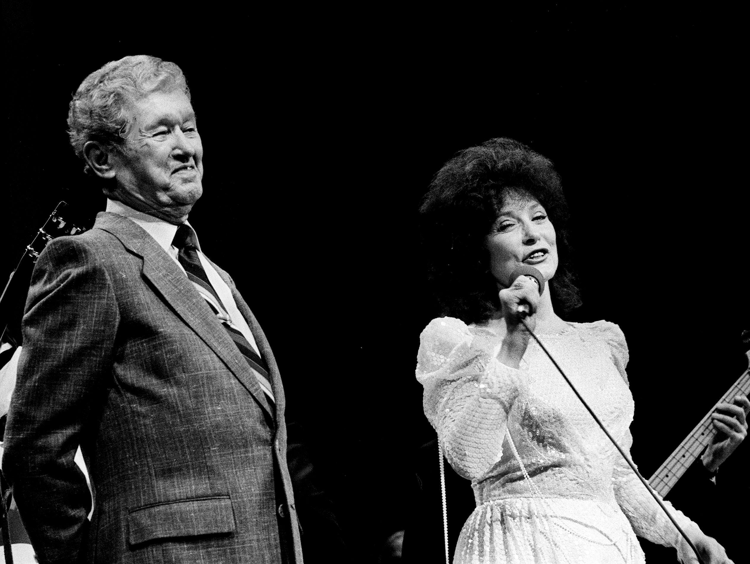 """Returning to the Grand Ole Opry stage Oct. 19, 1985 after an absence of four months, Roy Acuff, left, joins guest Loretta Lynn after he requested """"Coal Miner's Daughter"""" from her. A heart aliment had prevented the 82-year-old Acuff from performing."""