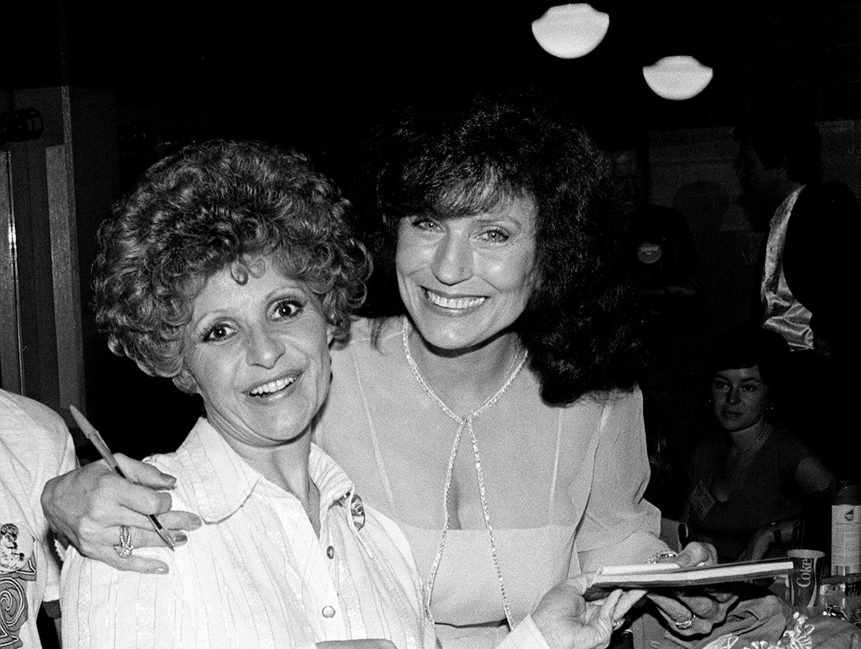 Brenda Lee, left, gets a hug and autograph from Loretta Lynn, who gets ready in the dressing room for the MCA Records show of the 10th annual International Country Music Fan Fair at the Municipal Auditorium in downtown Nashville June 11, 1981.