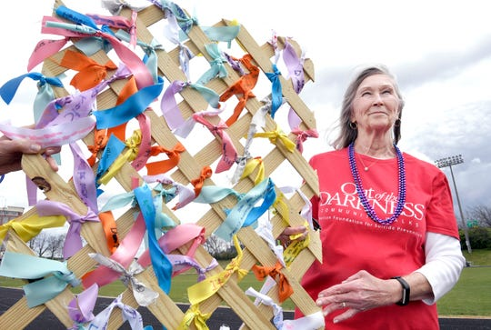 """Kathryn Squires helps organize the fourth annual """"Out of the Darkness"""" suicide awareness walk at Centennial High School in Franklin on March 30, 2019.  Squires stands next to a ribbon display on which people wrote messages regarding suicide."""