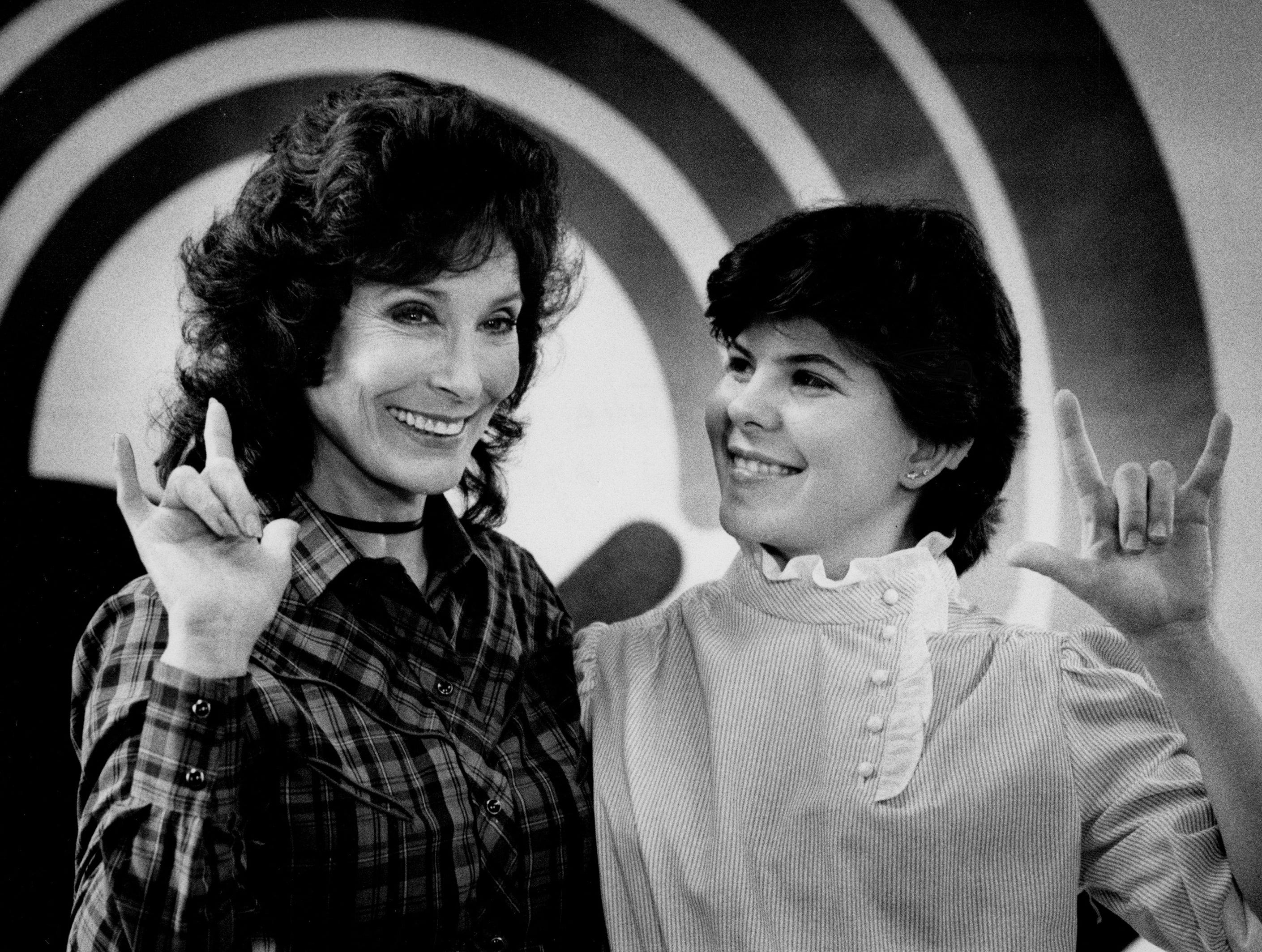 """Loretta Lynn, left, and Julie Bartee, 17, make the deaf sign for """"I Love You"""" during filming of United Way spot at the Bill Wilkerson Speech and Hearing Center April 3, 1984."""