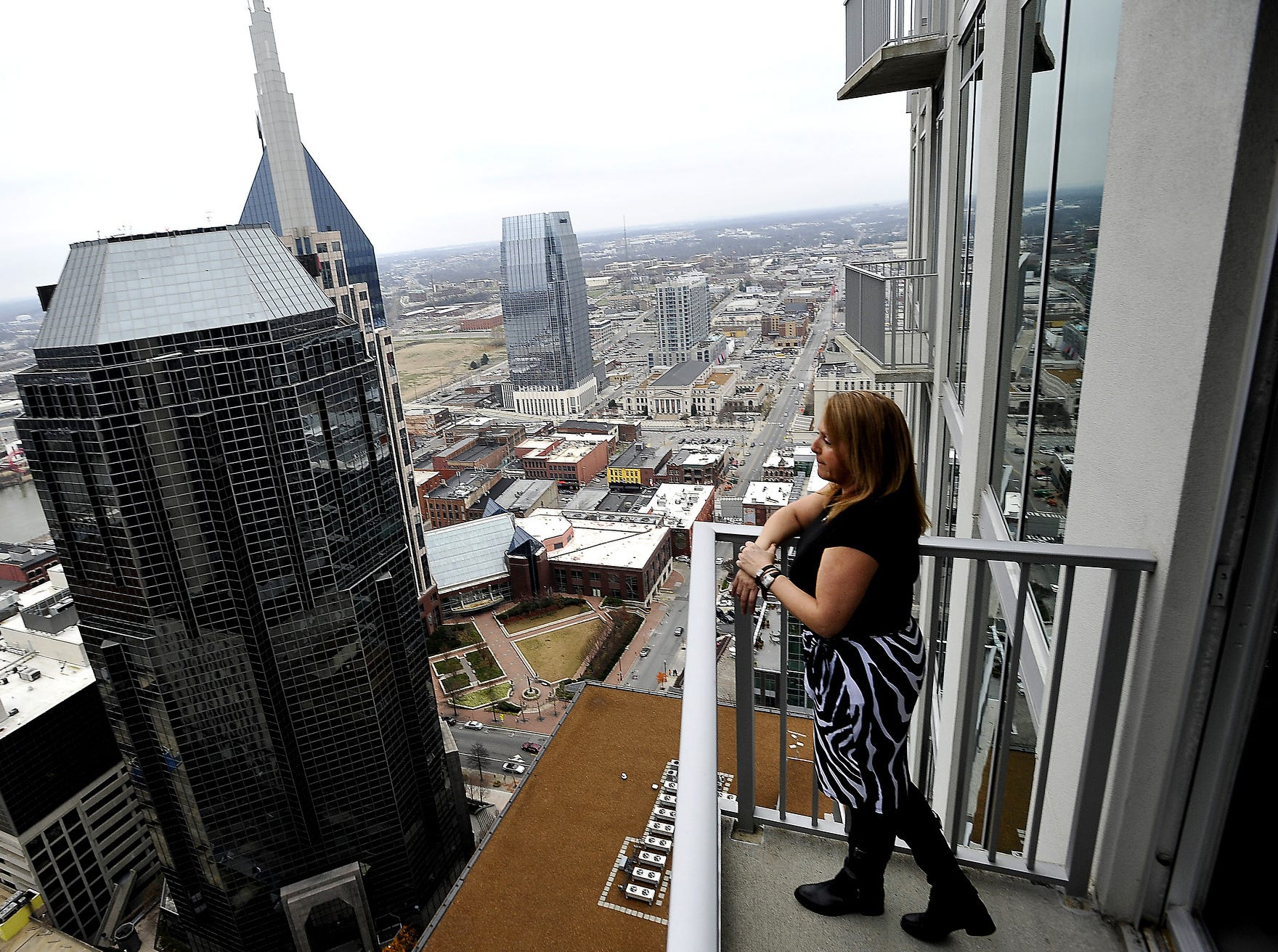 Laurie Sheinkopf, who used to live in a large house in Franklin, is enjoying the view of downtown Nashville from her condo in the Viridian building Dec. 23, 2011.