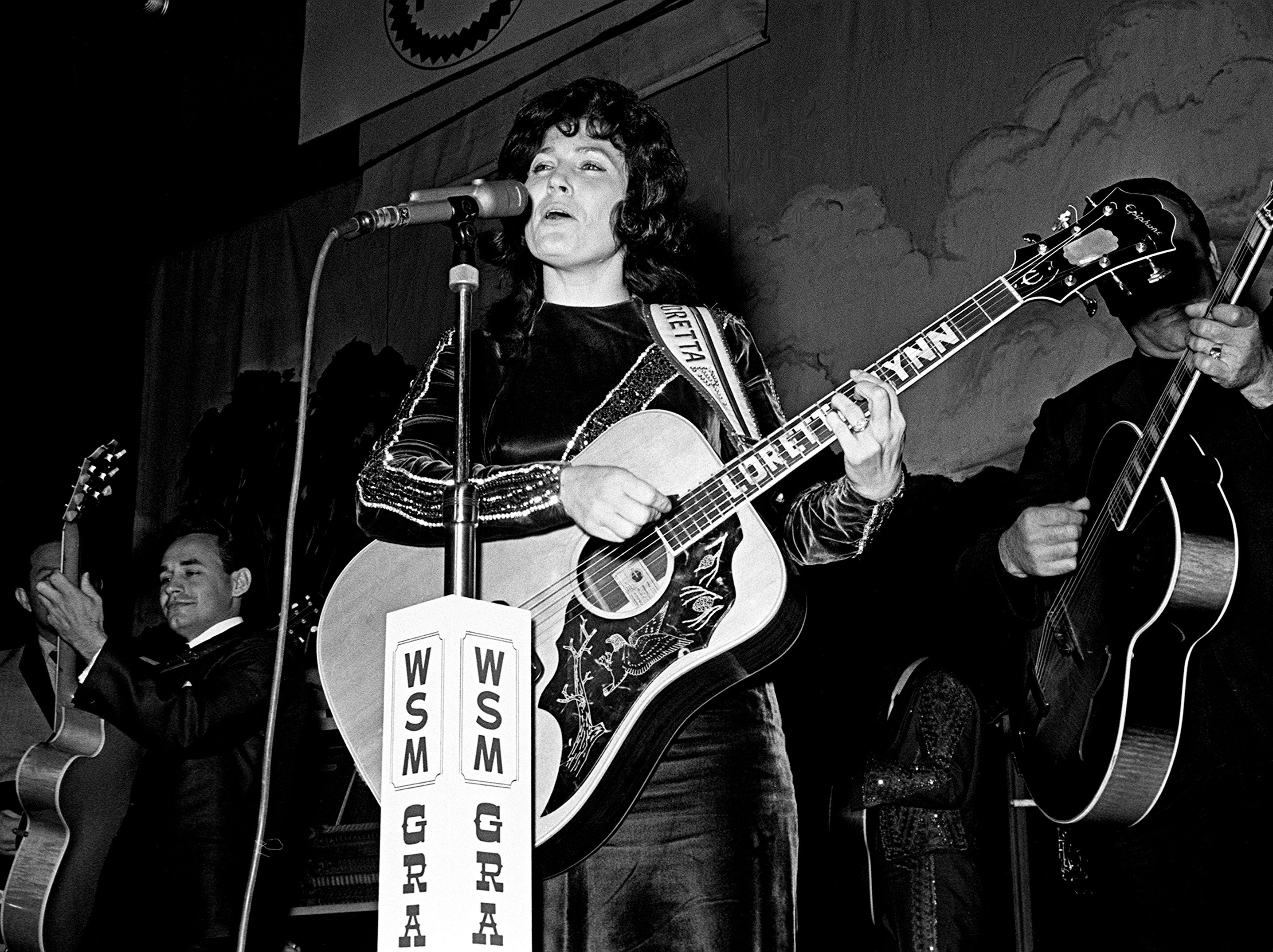 Loretta Lynn is performing for the crowd during a Saturday night Grand Ole Opry show at the Ryman Auditorium on Dec. 10, 1966.