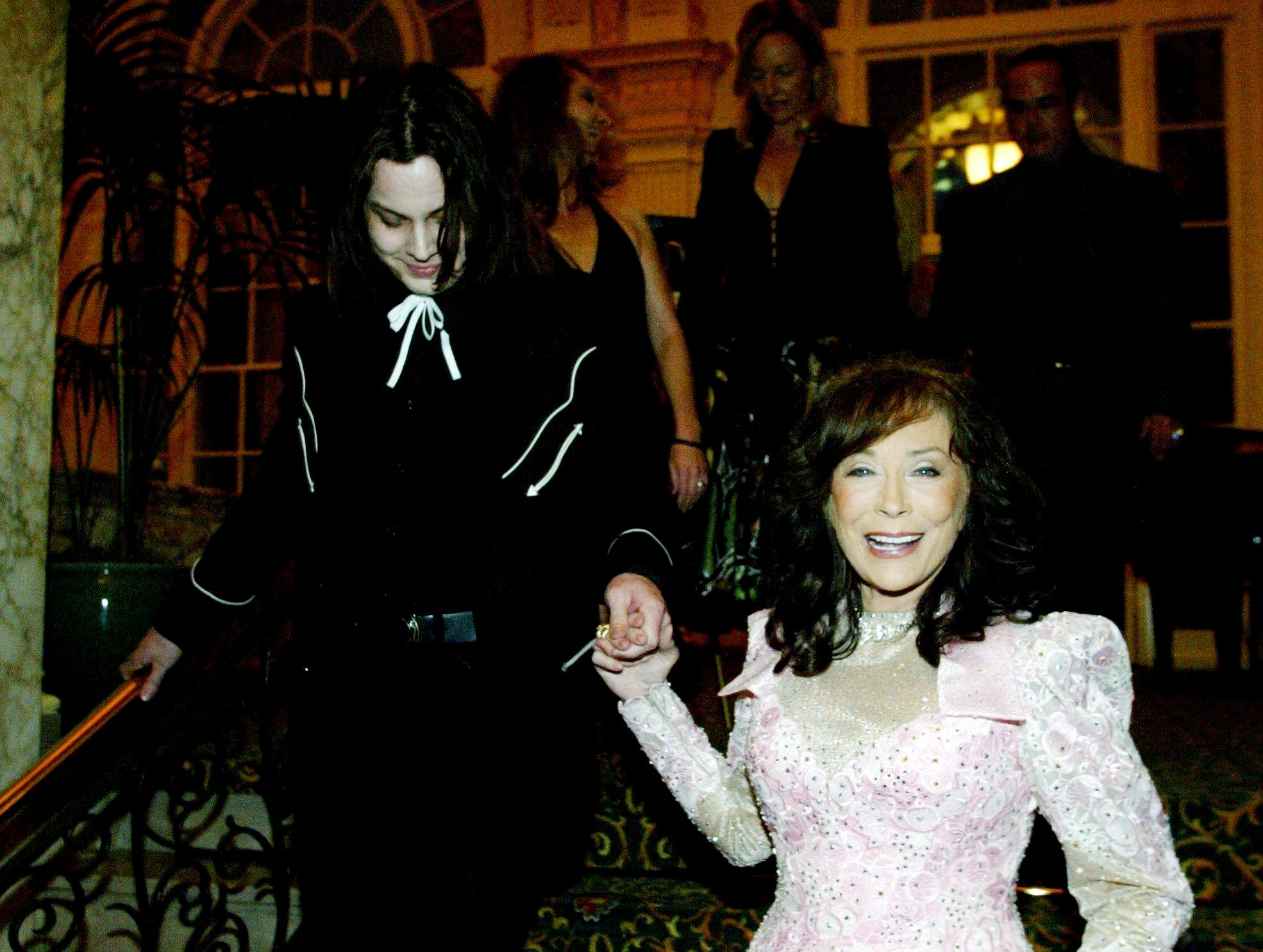 """Loretta Lynn, right, gets help down the stairs by White Stripes member Jack White during her new album release party at the Hermitage Hotel April 22, 2004. White was producer of Lynn's """"Van Lear Rose"""" album."""