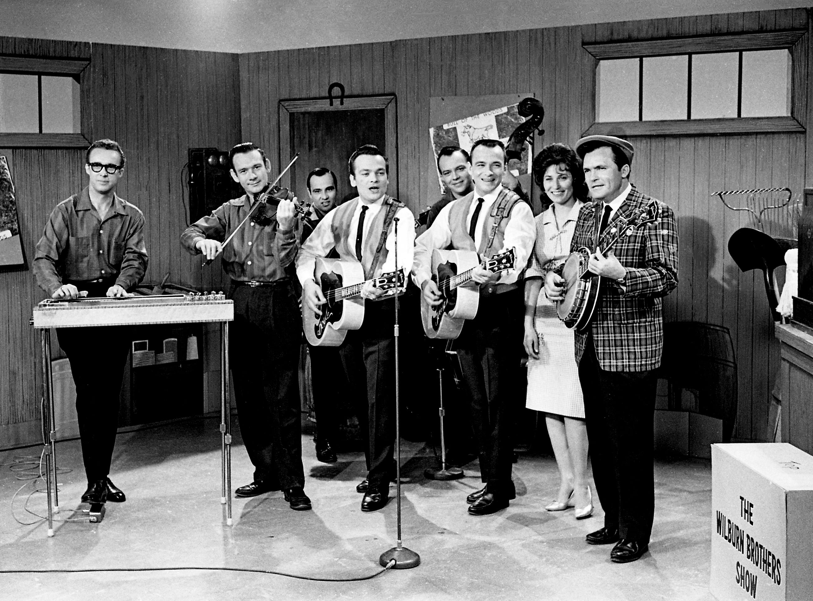 The Wilburn Brothers and their group make a tape of their new 30-minute weekly television show at WSM-TV on May 1, 1963. From left: they are Don Helms, steel guitar; Tommy Jackson, violin; Leslie Wilburn, rhythm guitar; singer Doyle Wilburn; Lester Wilburn, bass; singer Teddy Wilburn; singer Loretta Lynn; and Harold Morrison, banjo.