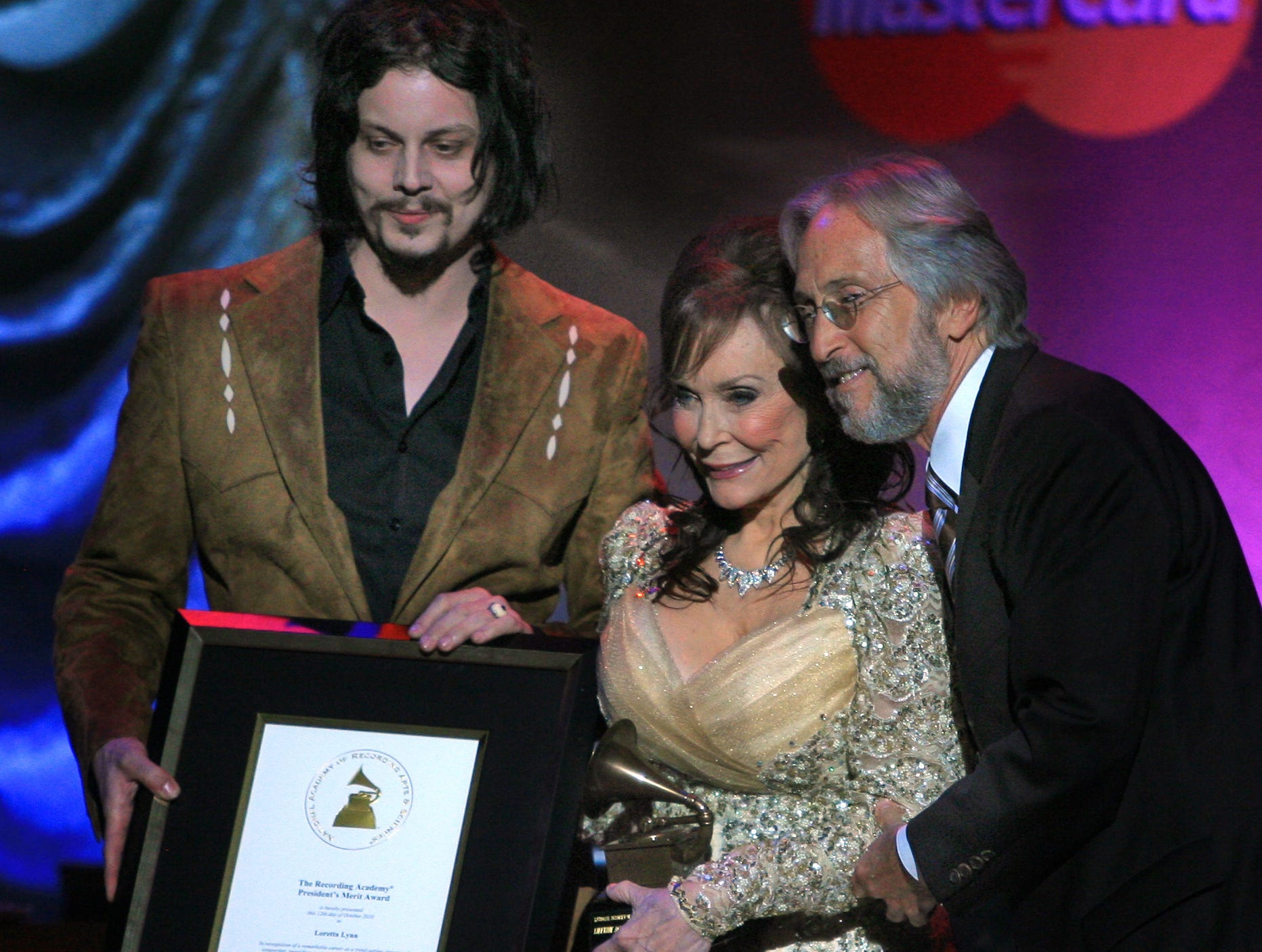 Eight time grammy winner Jack White, left, and the Recording Academy President and CEO Neil Portnow, right, present Loretta Lynn with a special presentation of the Recording Academy President's Merit Award in honor of her dynamic career and contributions to country music at the Ryman Auditorium Oct. 12, 2010 in Nashville.