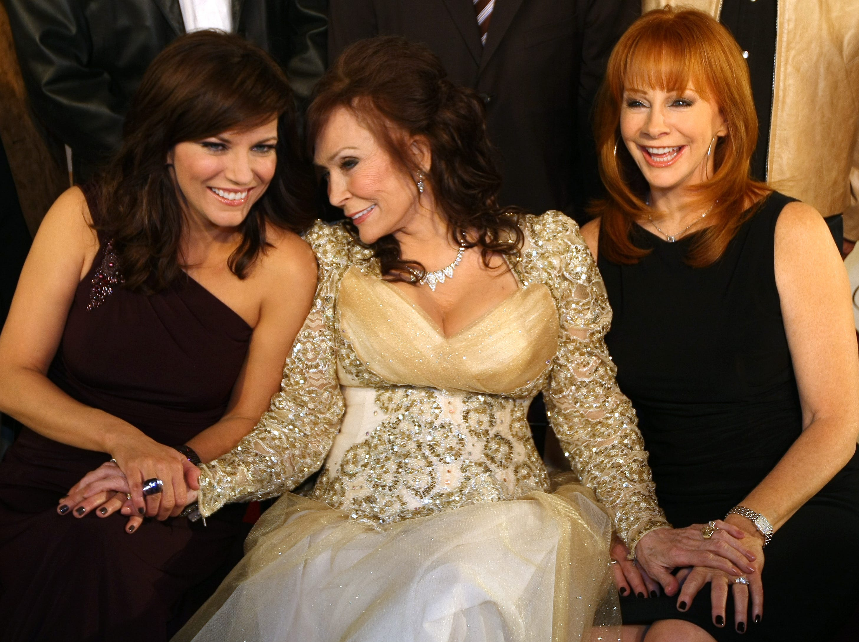 Recording artist Martina McBride, left, Loretta Lynn and Reba McEntire share a moment as they pose for a picture at the GRAMMY Salute To Country Music¨ honoring Lynn at the Ryman Auditorium Oct. 12, 2010 in Nashville.
