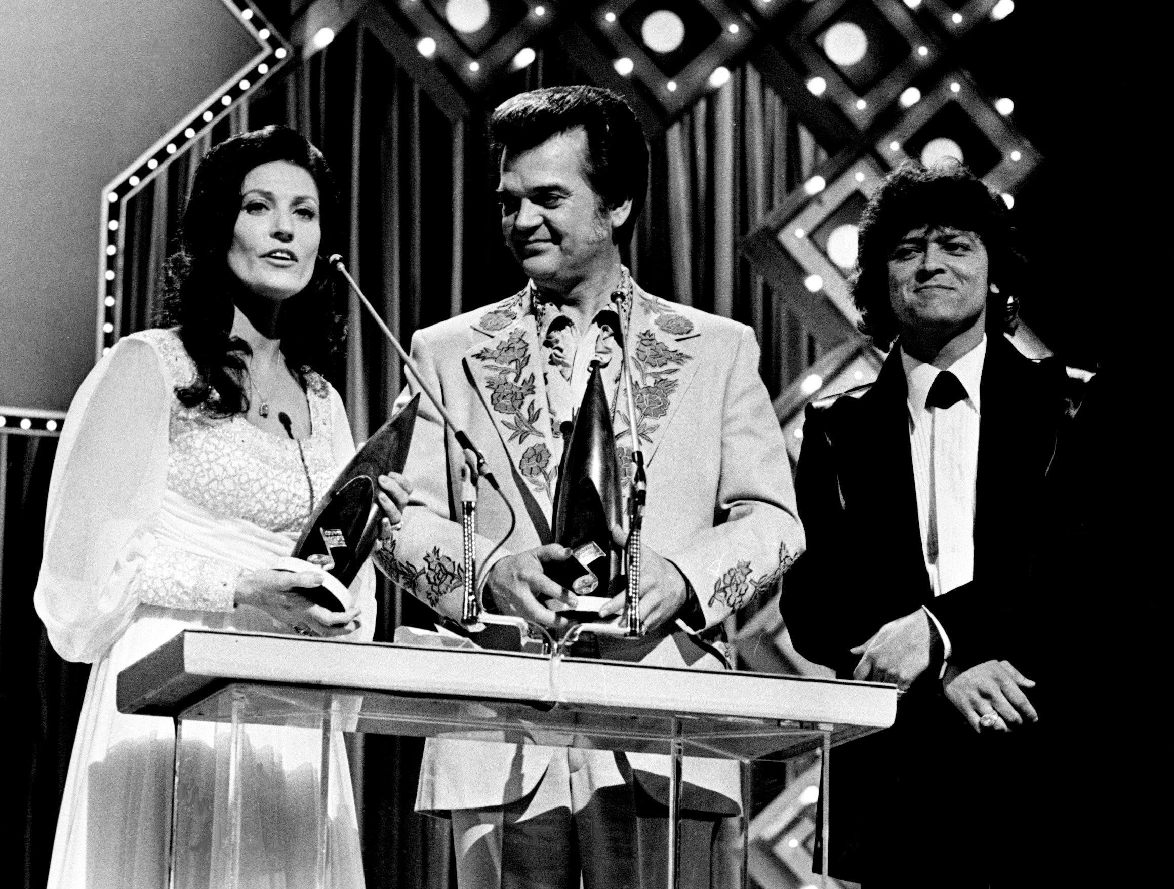 Loretta Lynn, left, and Conway Twitty win the Vocal Duo of the Year award at the nationally televised CMA Awards show Oct. 13, 1975, as presenter Johnny Rodriguez, right, looks on.