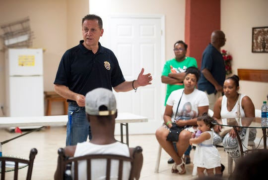 Paterson Police Director Jerry Speziale addressed those gathered at a Stop the Violence informational meeting on July 23, 2014, hosted by the Rev. Della Fischer, pictured standing at right, and her husband, Mark Fischer, at their home on Montgomery Street. Jenny Calderon, seated far right, the mother of Genesis Rincon, attended with her daughter Hailee, 16 months, as well as community members and representatives of faith-based organizations, civic organizations and local businesses.
