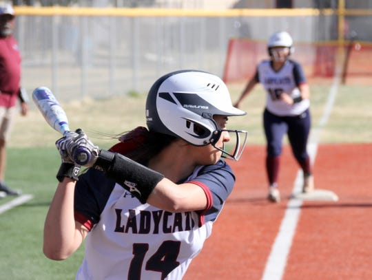 Junior Lady 'Cat Chloe Johnson (14) eyes a pitch at the plate with freshman Nayeli Trujillo standing on third base.