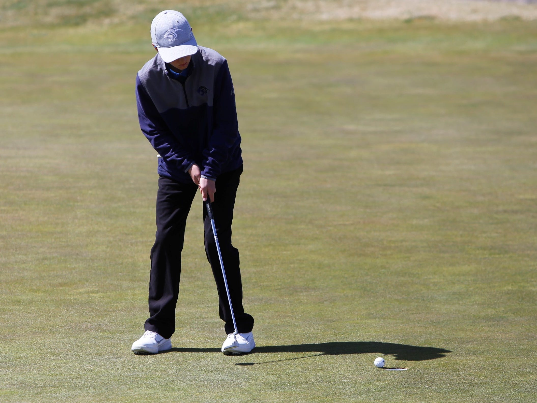 Piedra Vista's Matt Ahlgrim sinks his putt on the 10th green during Monday's Shiprock Invitational at Riverview Golf Course in Kirtland.