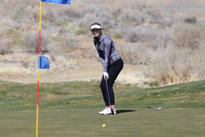 Aztec's Madyson Current watches her ball inch closer to the hole putting on the 10th green during Monday's Shiprock Invitational at Riverview Golf Course in Kirtland.