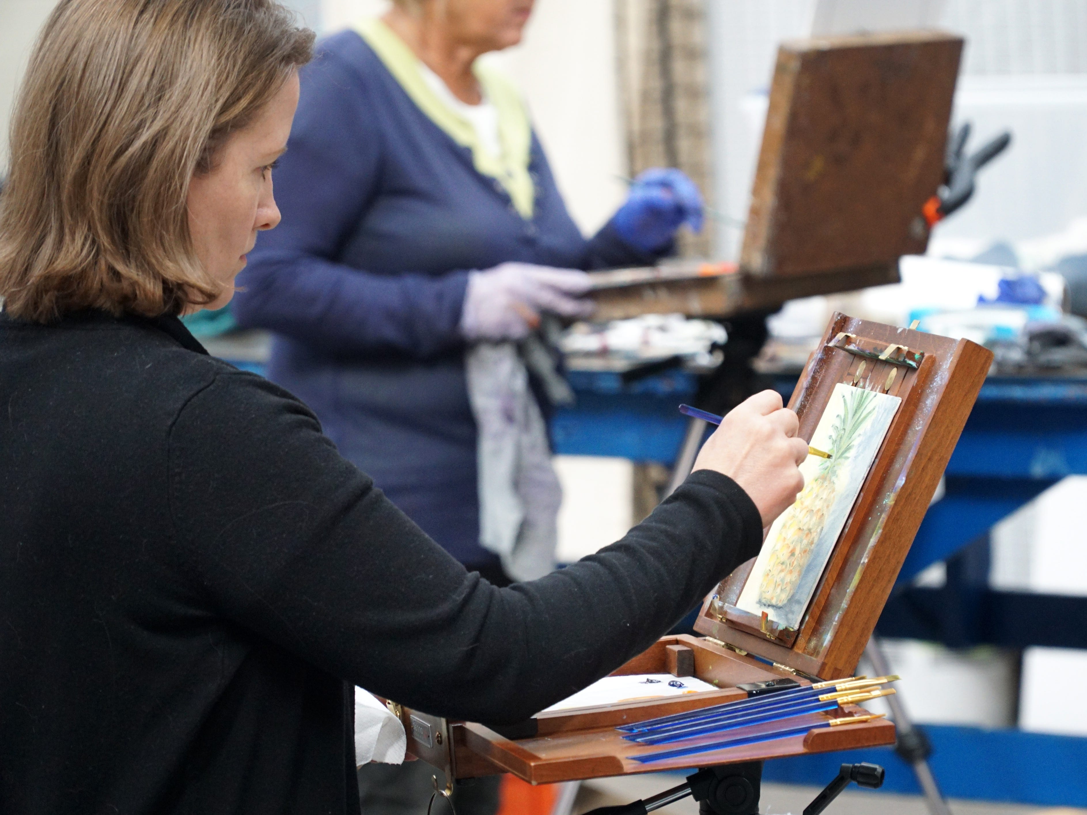 Tammy Ware, of Highland, works on her oil painting of a still life of a pineapple during an April 1 class at Milford's SHAC.