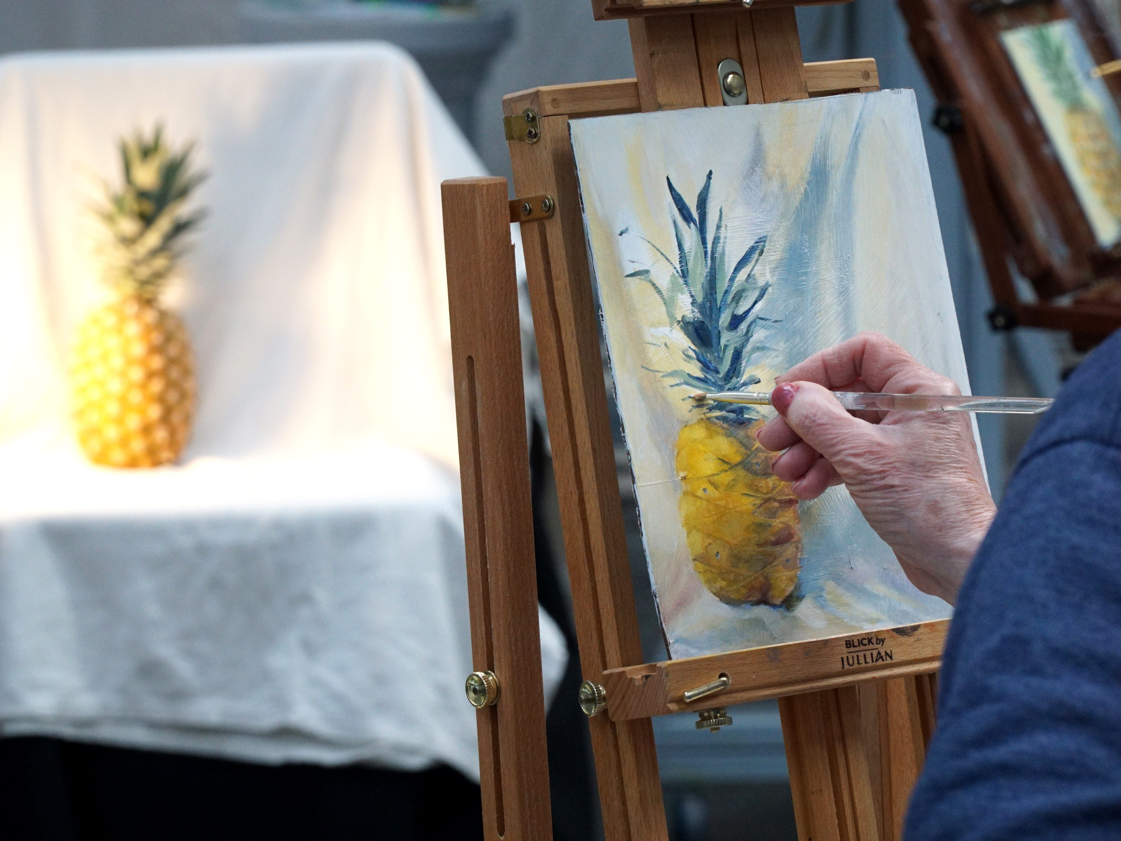 Todoroff works on his oil painting of a pineapple.