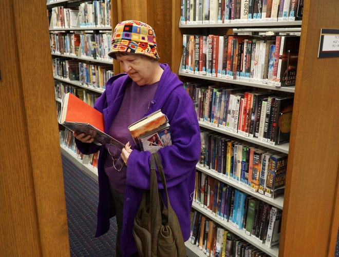 Lin Beckhold checks out some potential mystery novels on April 1 at the Redford Township District Library. Beckhold said at that time that she'd already heard that the library was no longer going to collect fines on overdue books and other materials - and was fine with that as she checks out a lot of literature and films from the library.