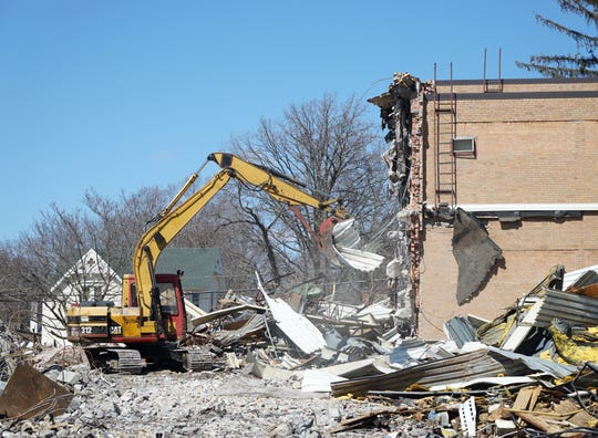 A backhoe continues the work on tearing down the Northville Main Street School on April 1. About one half of the structure has been demolished and removed from the grounds. Work is slated to continue until early May.