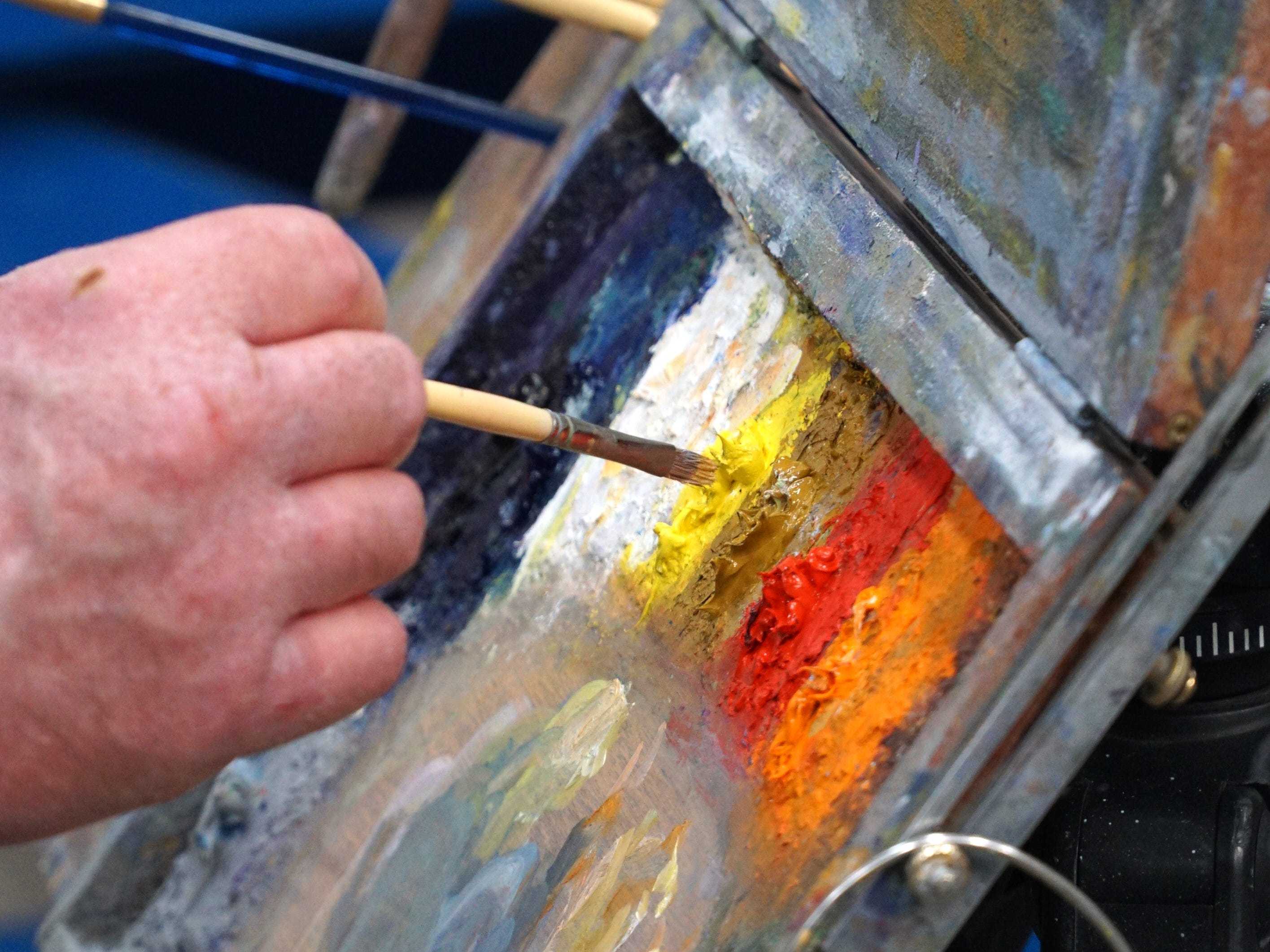 Mike Todoroff gets some yellow oil paint from his palette during his April 1 class at Milford's SHAC.