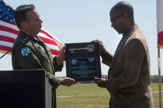 Cmdr. Jim Brownlee, executive officer of Naval Air Station Whiting Field, presents Escambia County Commissioner Lumon May with the key to the Navy's former Outlying Landing Field 8 during a ceremony Monday to commemorate the land swap.